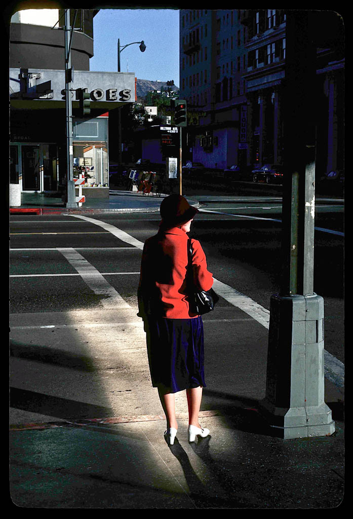 Woman in shaft of sunrise reflected light on Hollywood waits for bus.