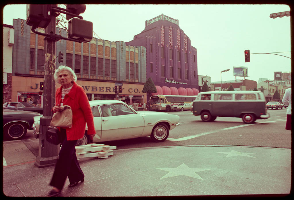 Women crosses street in across from Frederick's of Hollywood and Newberry's