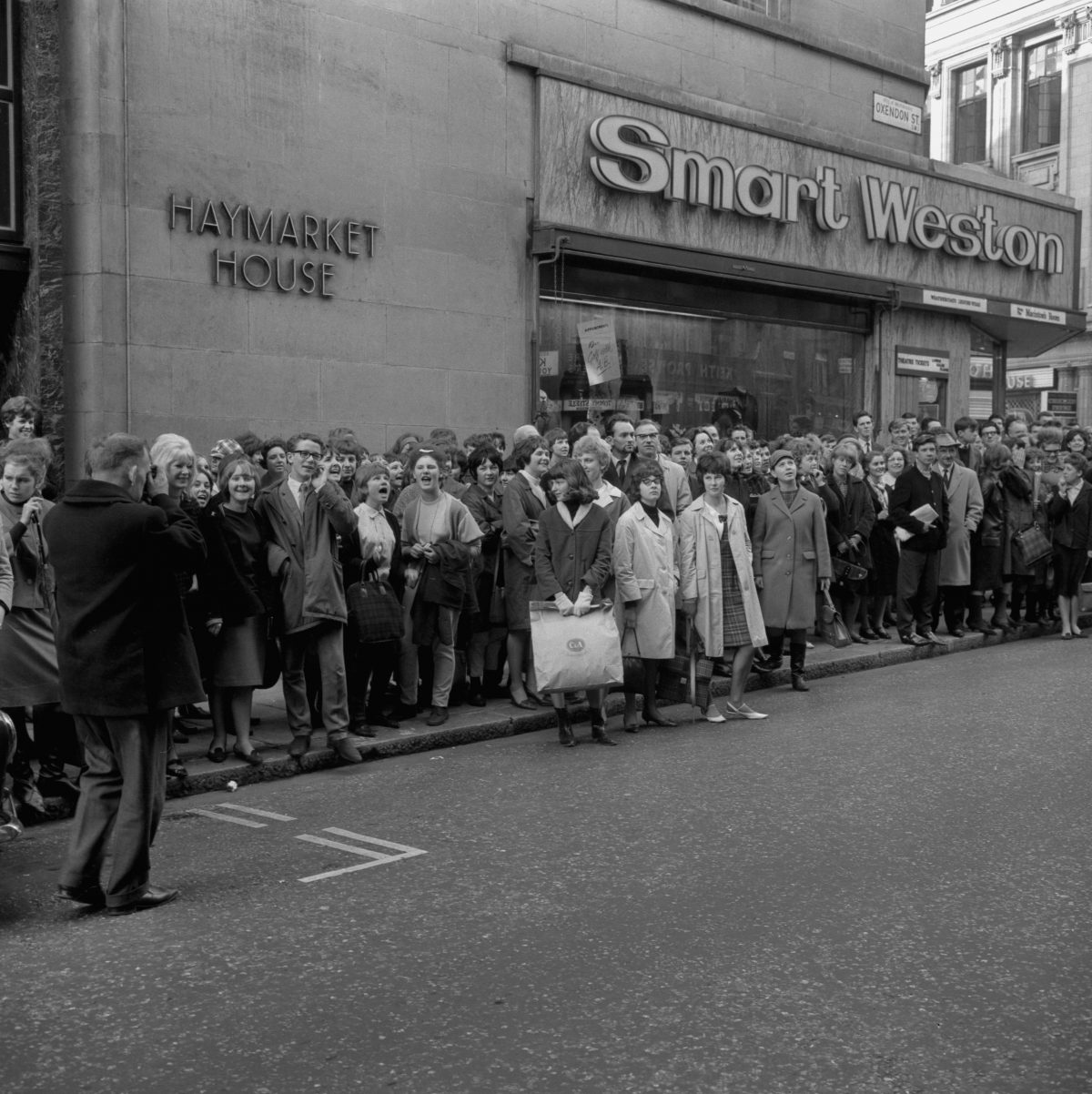 Beatles fans outside the Prince of Wales Theatre in London wait to catch a glimpse of their idols who were taking part in rehearsals for tonight's Royal Variety Performance.