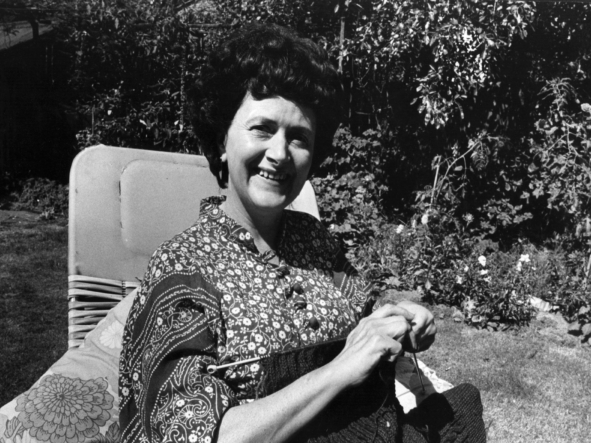 Cynthia knitting in the garden of 32 Ambleside Avenue