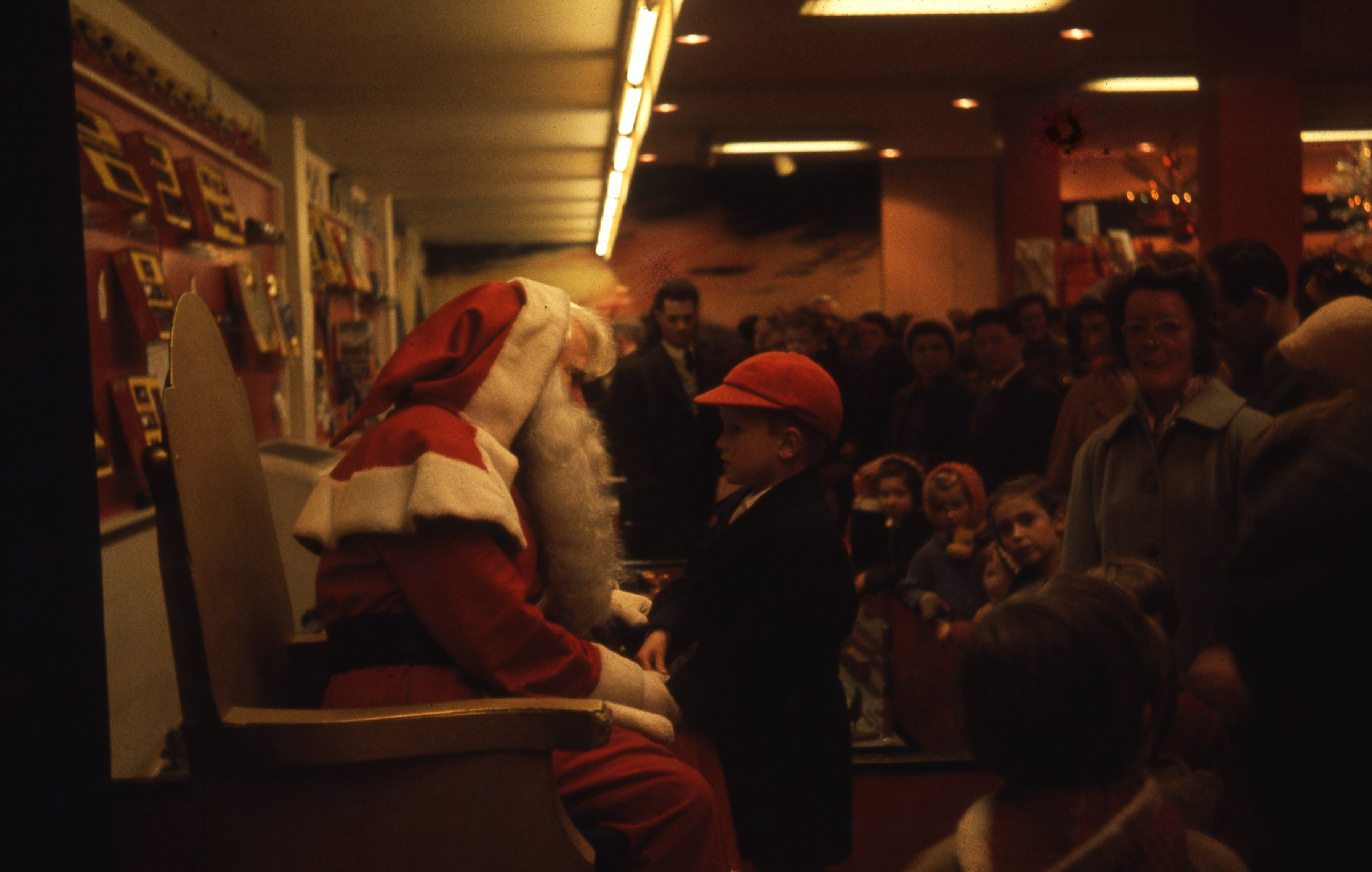 This photograph shows Santa's Grotto in the Fenwick department store in Newcastle upon Tyne. Children and their parents wait to meet Father Christmas. This is a 35mm slide. It was taken in 1962.