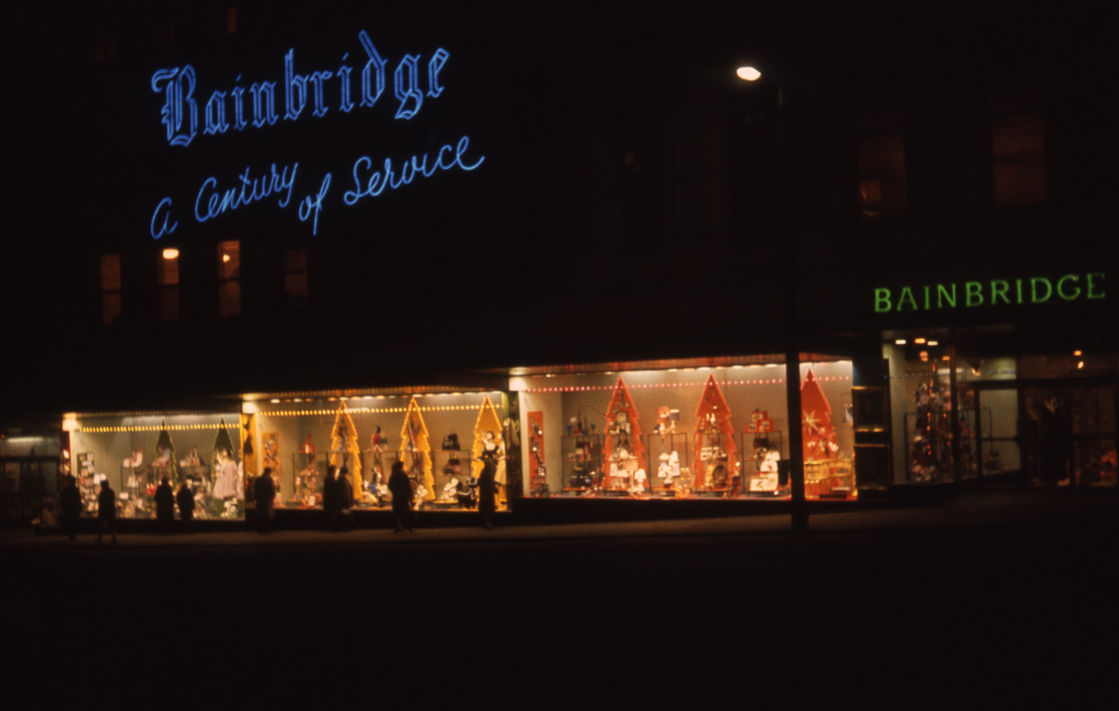 "It shows a view of the decorated Christmas window of Bainbridge's in Newcastle upon Tyne. The sign reads ""Bainbridge, a century of service."" This is a 35mm slide. It was taken in 1962."