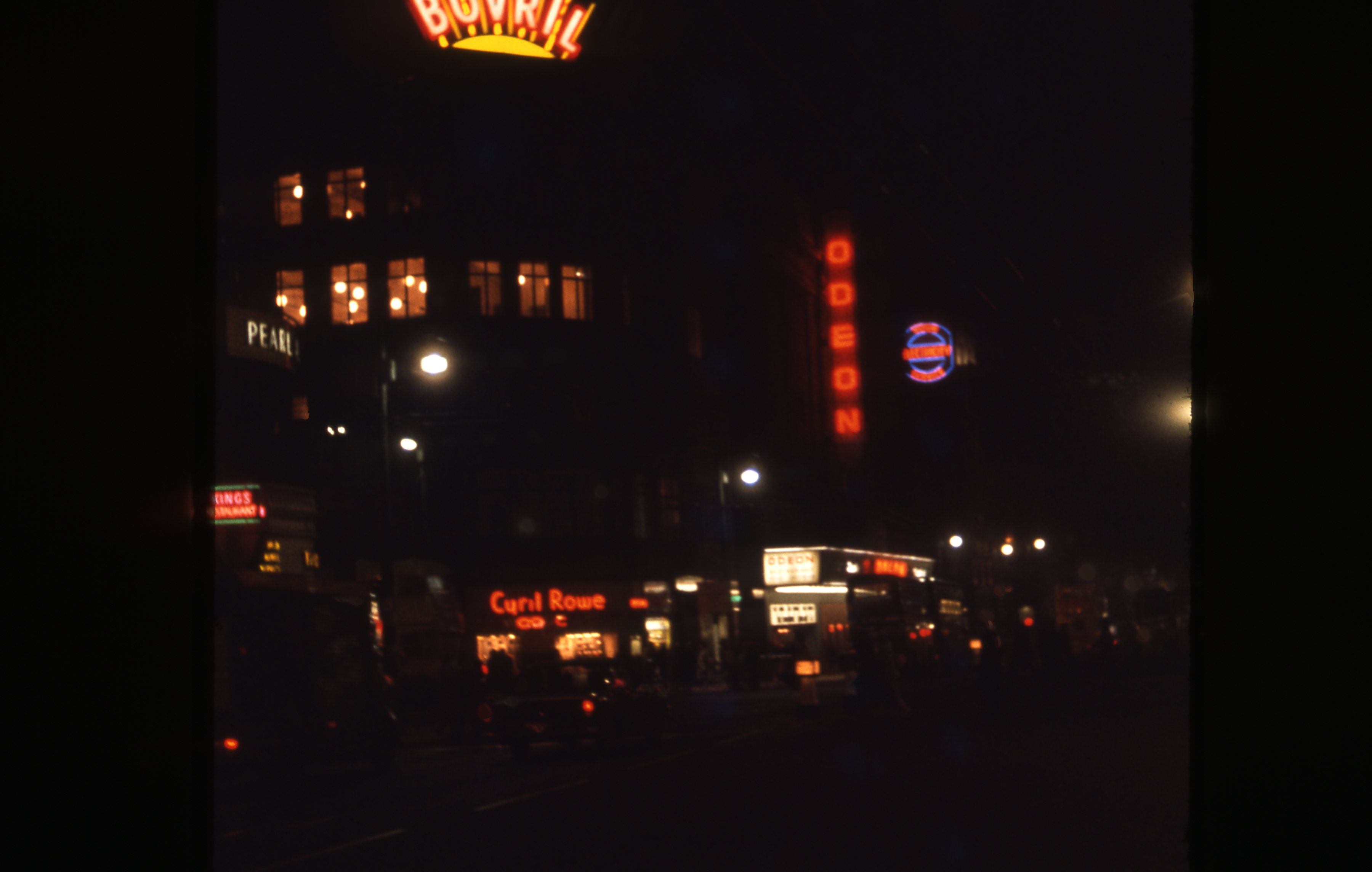 This is a night view of Northumberland street, Newcastle upon Tyne. It is illuminated by many festive commercial signs and decorations. This is a 35mm slide. It was taken in 1962.