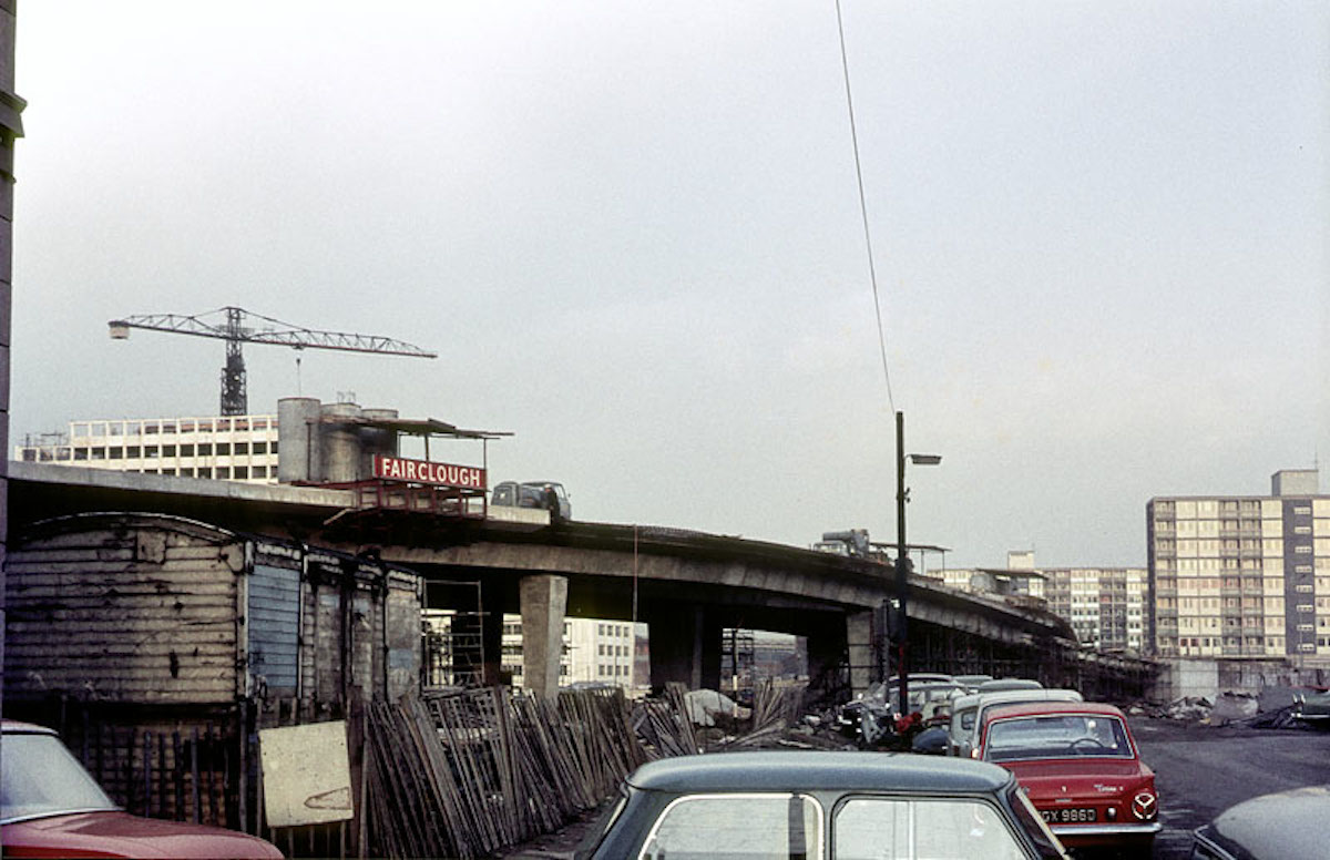 The elevated section of the Mancunian Way under construction in 1966. The tower of UMIST's Faraday Building, also under construction, can be seen rising beyond the flyover on the left of the picture.