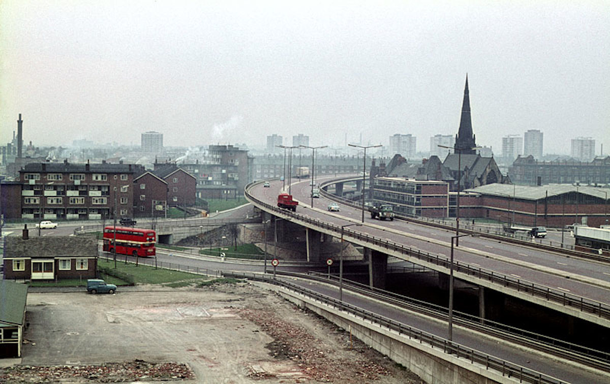 The elevated section of the Mancunian Way and adjoining slip road at All Saints, c. 1968. Taken from the Cavendish School on Loxford Street looking west towards north Hulme. The space in the foreground was subsequently occupied by the Loxford Tower (completed in 1974), and is now the site of the new MMU Business School.