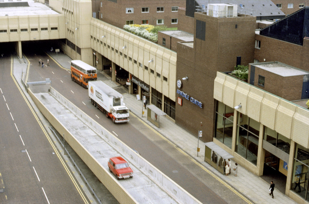 Exterior of the Manchester Arndale Centre showing the facade of the north section fronting on to Cannon Street. The bridge carrying the upper shopping mall over Cannon Street at the junction with Corporation Street can be seen at the top left of the picture, and the entrances to the bus station and the indoor market are also visible. Photographed in May 1985.
