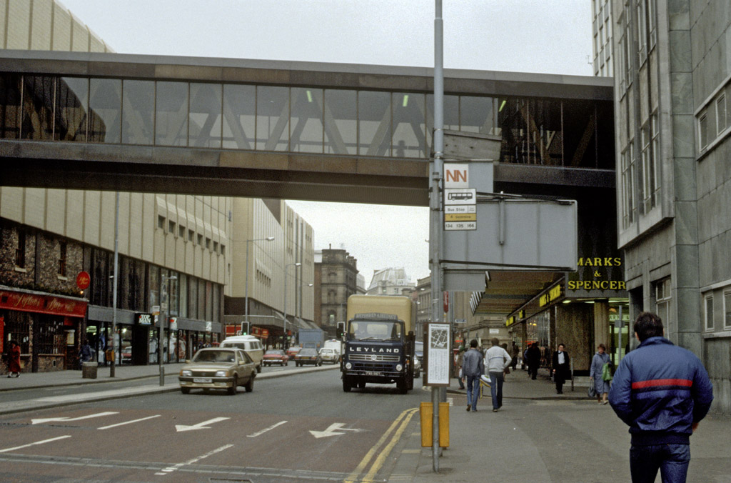 View along Corporation Street looking south towards Cross Street, showing the west facade of the Arndale Centre on the left of the picture. The footbridge linking the Arndale Centre to Marks & Spencer's and Market Square can be seen at the top of the picture. Photographed in May 1985, close to the spot where the IRA bomb exploded on 15th June 1996. The architect for the centre was Wilson & Womersley