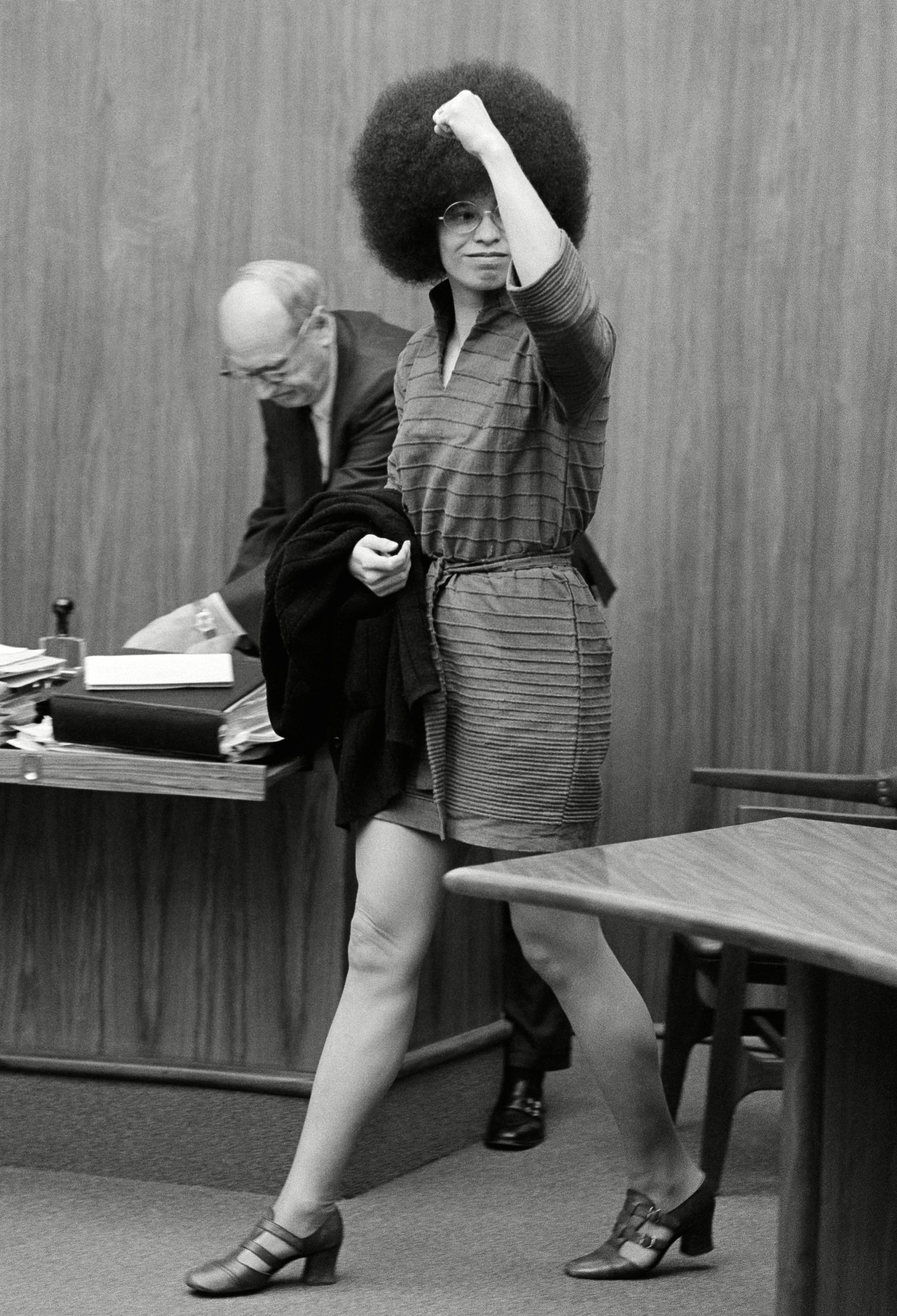 Angela Davis waves to someone in the audience as she arrives the room in San Rafael, Calif. for another pre-trial hearing. At left is chief attorney, Howard Moore Jr of Atlanta. holding the door Miss Davis is Capt. Harvey Teague of the Marin County Sherriffs Department Angela Davis, San Rafael, USA
