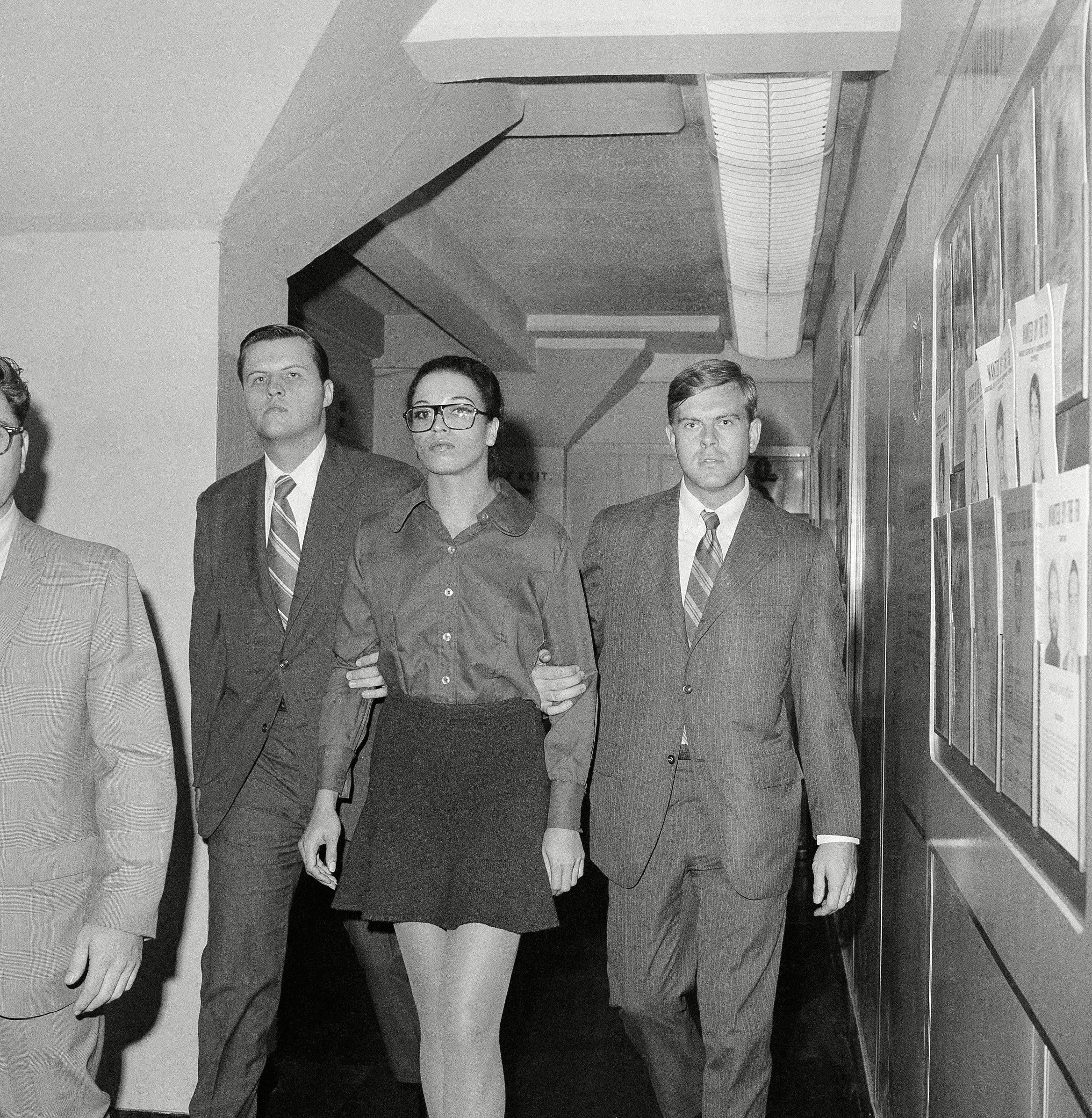 Angela Davis, first woman ever listed among the FBI's Ten Most Wanted Fugitives, is escorted by two FBI agents after her arrest in New York on . She was being taken from FBI headquarters to the Women's House of Detention. Wanted in connection with the August 7 California courtroom kidnapping, she was arrested in a midtown New York motel 13 Oct 1970