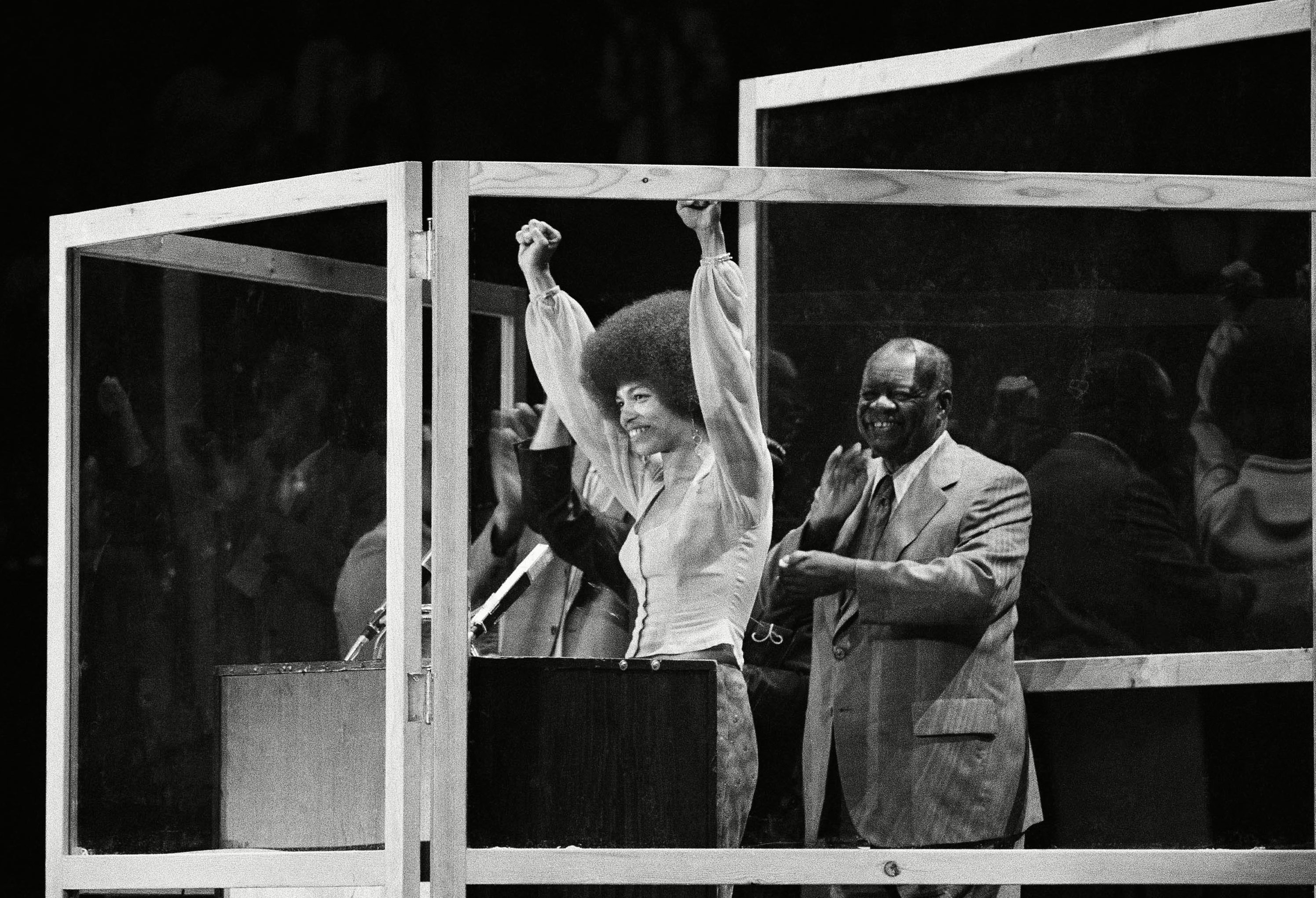 "Angela Davis raises her arms in greetings after being introduced by Henry Wins right, to the audience at ""An evening with Angela Davis"" benefit at New York's Madison Square Garden . They are standing in a special bullet-proof four-sided clear plastic booth which was set in place on the Garden's stage for Davis' speech 28 Jun 1972"
