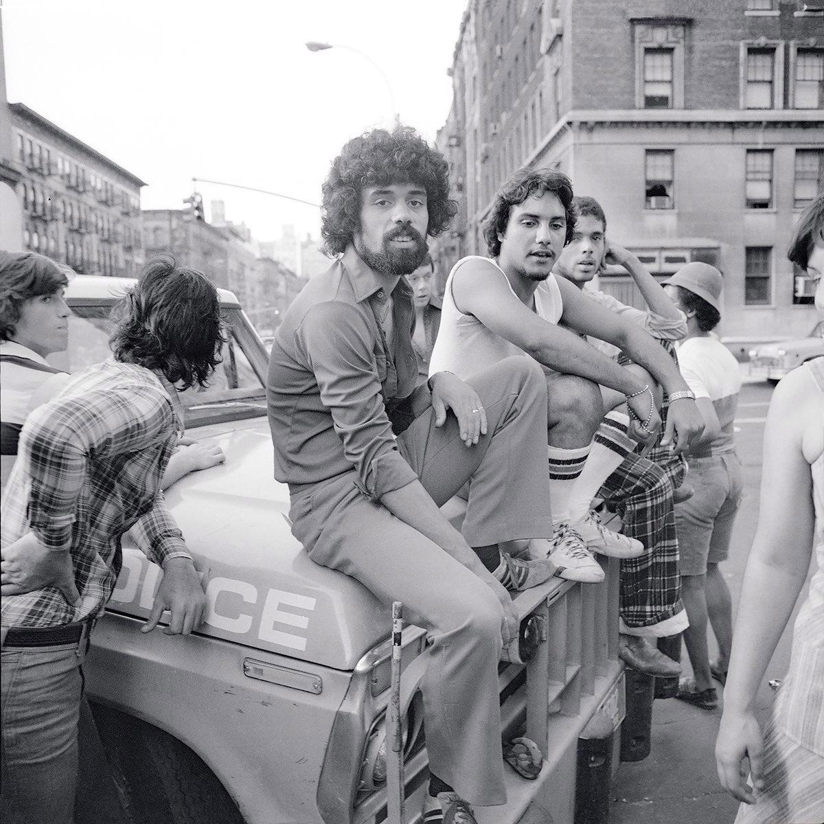 During the New York City blackout of 1977, Meryl Meisler captured this photo of a group of guys hanging out on the hood of a police car in New York City on July 13, 1977.