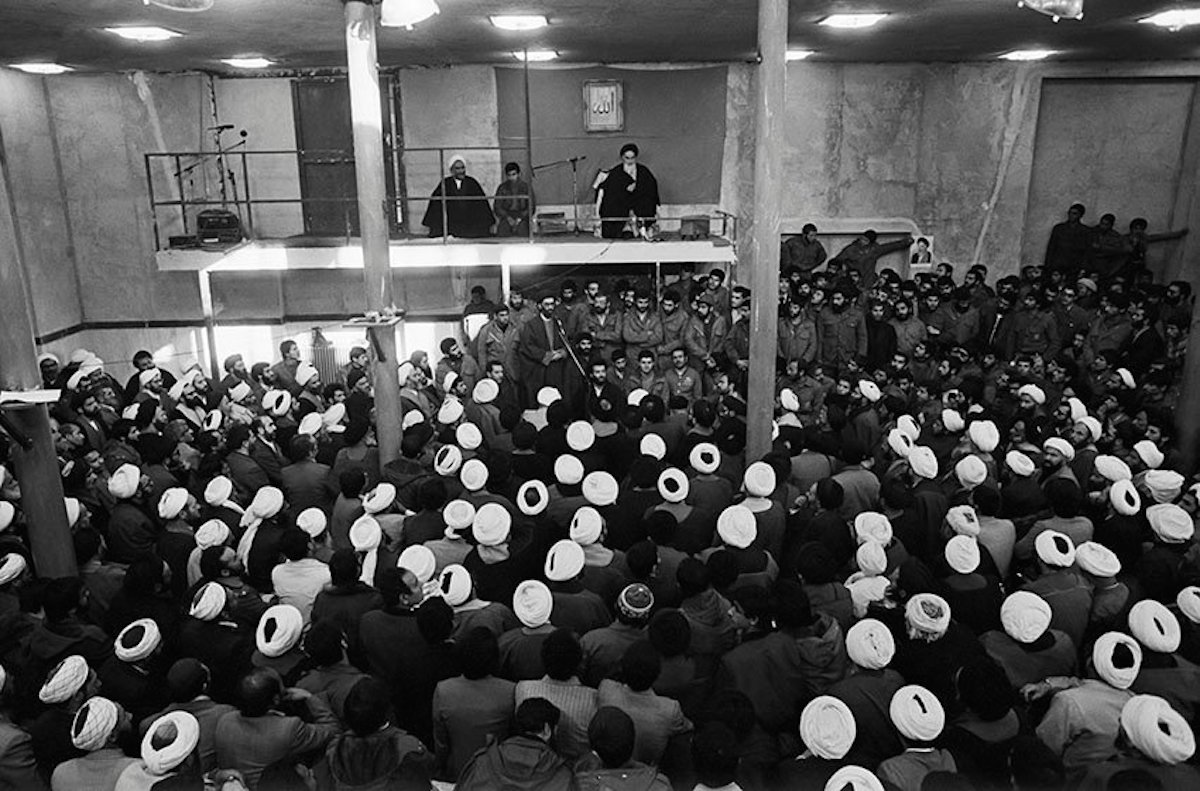 Ayatollah Khomeini, sitting on a balcony to the right, addressing clergymen who came to Jamaran mosque to see him on March 1, 1982.