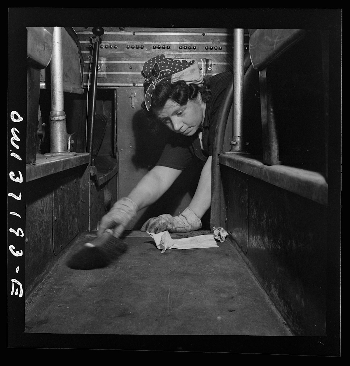 Pittsburgh, Pennsylvania. A charwoman who cleans buses sweeping the floor of a bus at the Greyhound garage