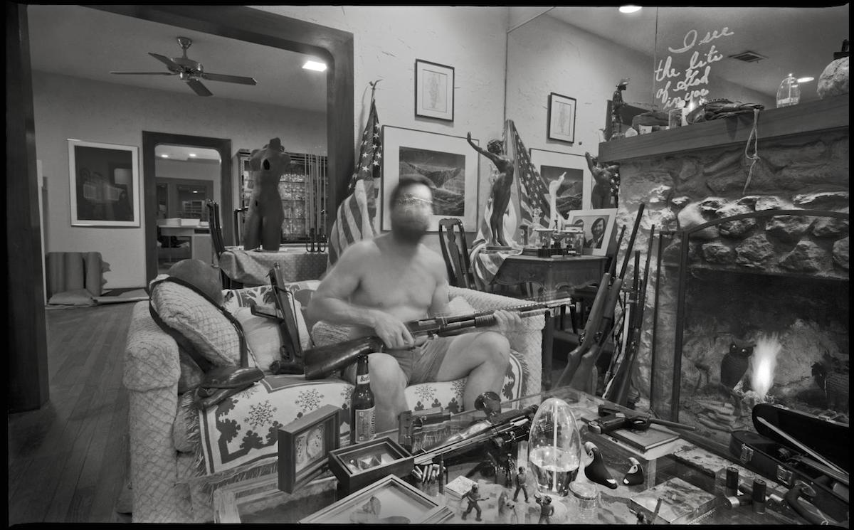 "Photograph of a man sitting in his living room with a gun on his lap. Written in lipstick on a mirror is ""I see the lite of God in you."" DATE: 1985 CREATOR: Williams, Byrd M. (Byrd Moore), IV, 1951-"