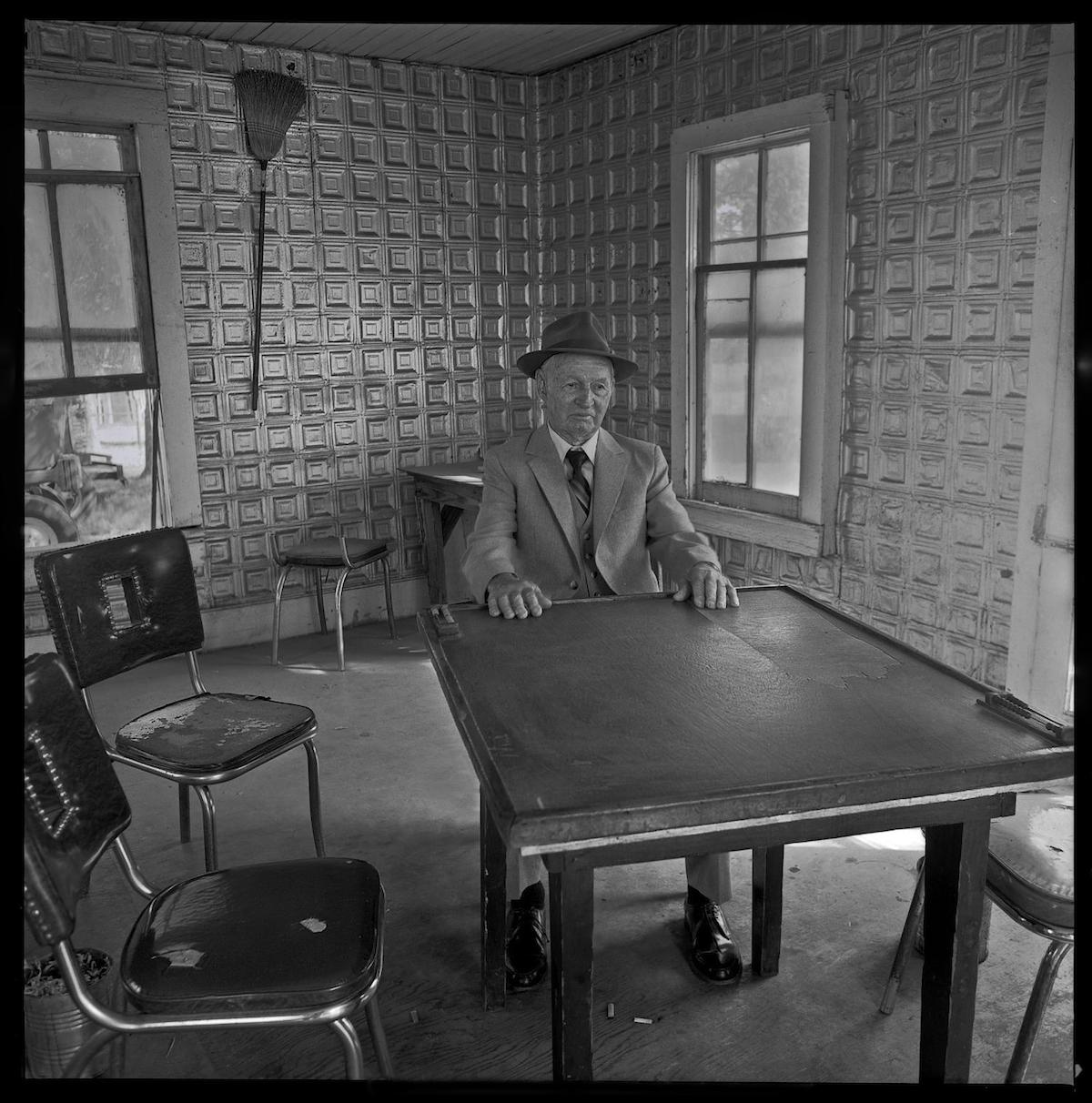 Photograph of a man sitting at a table in a domino parlor. DATE: 1985~ CREATOR: Williams, Byrd M. (Byrd Moore), IV, 1951-