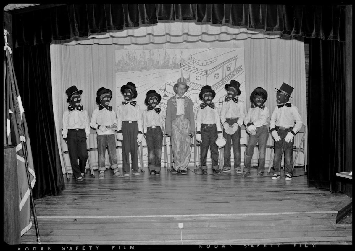 Photograph of a group of children wearing black face masks to perform a blackface play. CREATOR: Williams, Byrd M. (Byrd Moore), III