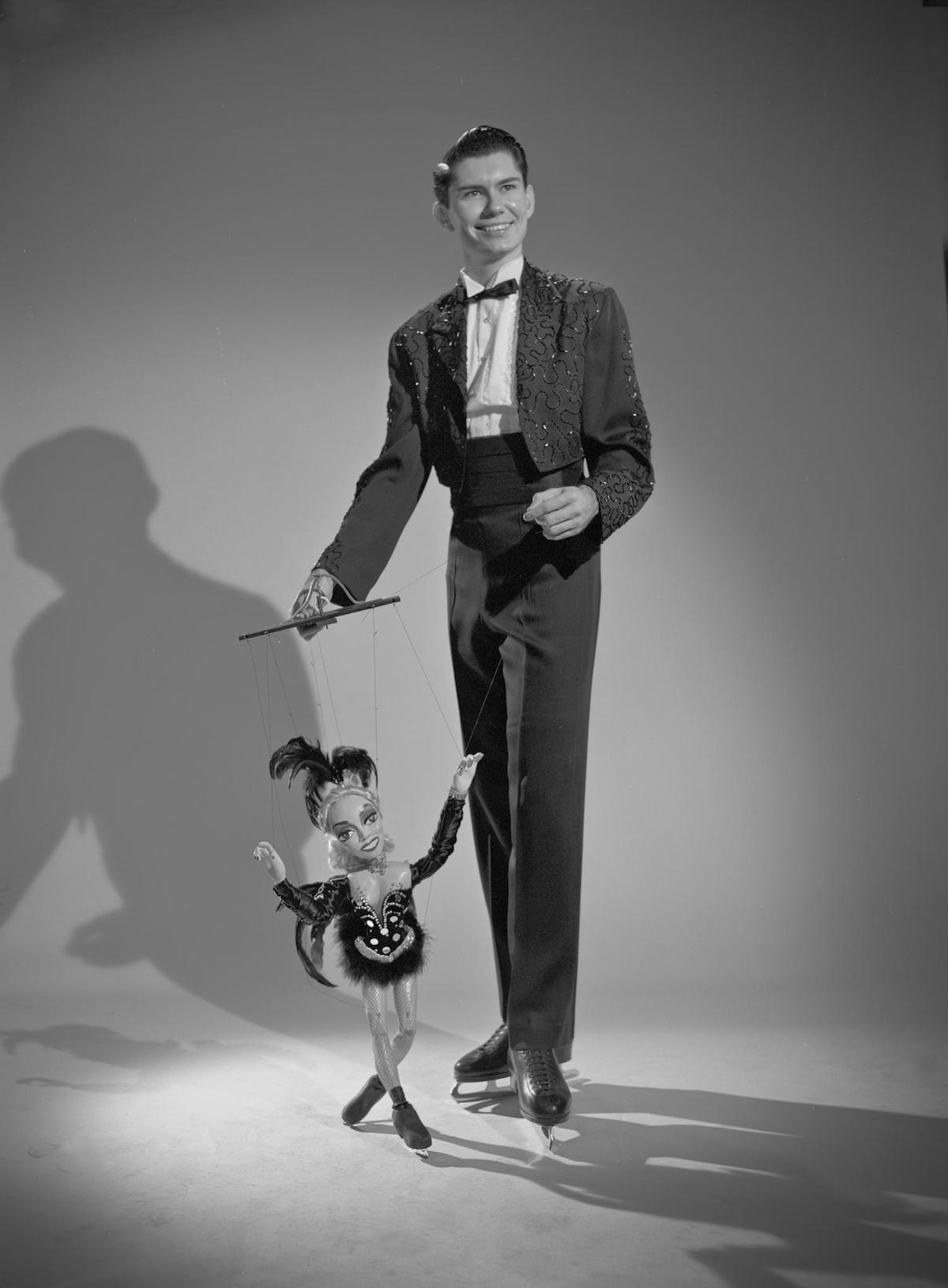 Photograph of a man named Jack Hines posing for a portrait wearing ice skates and holding a marionette. DATE: 19uu CREATOR: Williams, Byrd M. (Byrd Moore), III