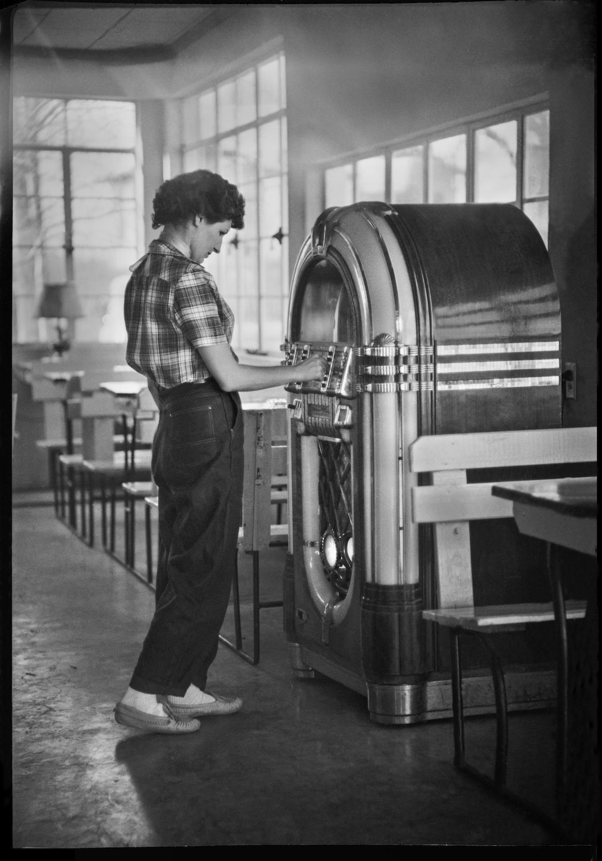 Photograph of Byrd Williams III's wife, Doris Stiles Williams, standing at a jukebox in Corpus Christi, Texas. DATE: 1948 CREATOR: Williams, Byrd M. (Byrd Moore), III