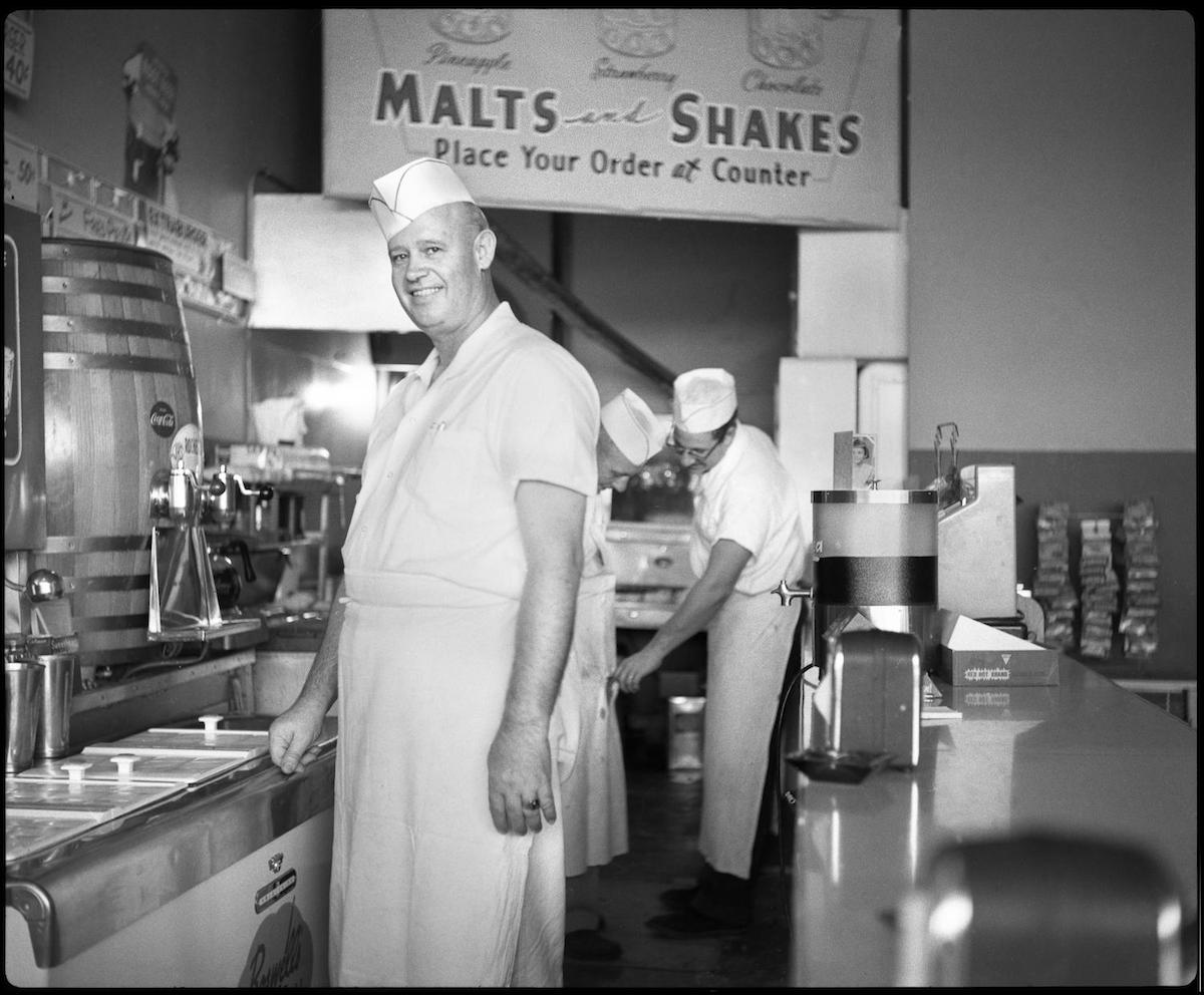 Photograph of Ernie Morgan, owner of a hamburger stand in Fort Worth, cooking with his employees. DATE: 1954 CREATOR: Williams, Byrd M. (Byrd Moore), III