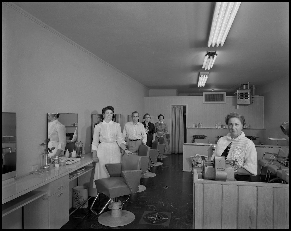Photograph of five employees of a beauty salon posing at their workstations. 1950s