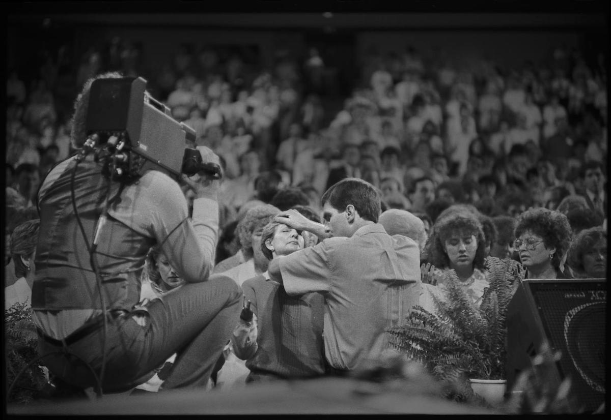 Photograph of a televangelist praying for a woman in a large crowd with a cameraman taping. CREATOR: Williams, Byrd M. (Byrd Moore), IV, 1951-