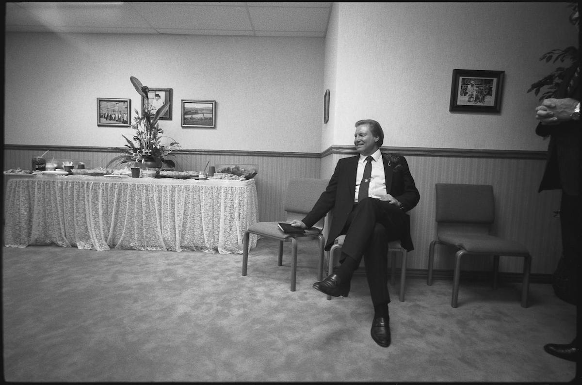 Photograph of televangelist Jimmy Swaggart sitting on a chair in a reception room. CREATOR: Williams, Byrd M. (Byrd Moore), IV, 1951-