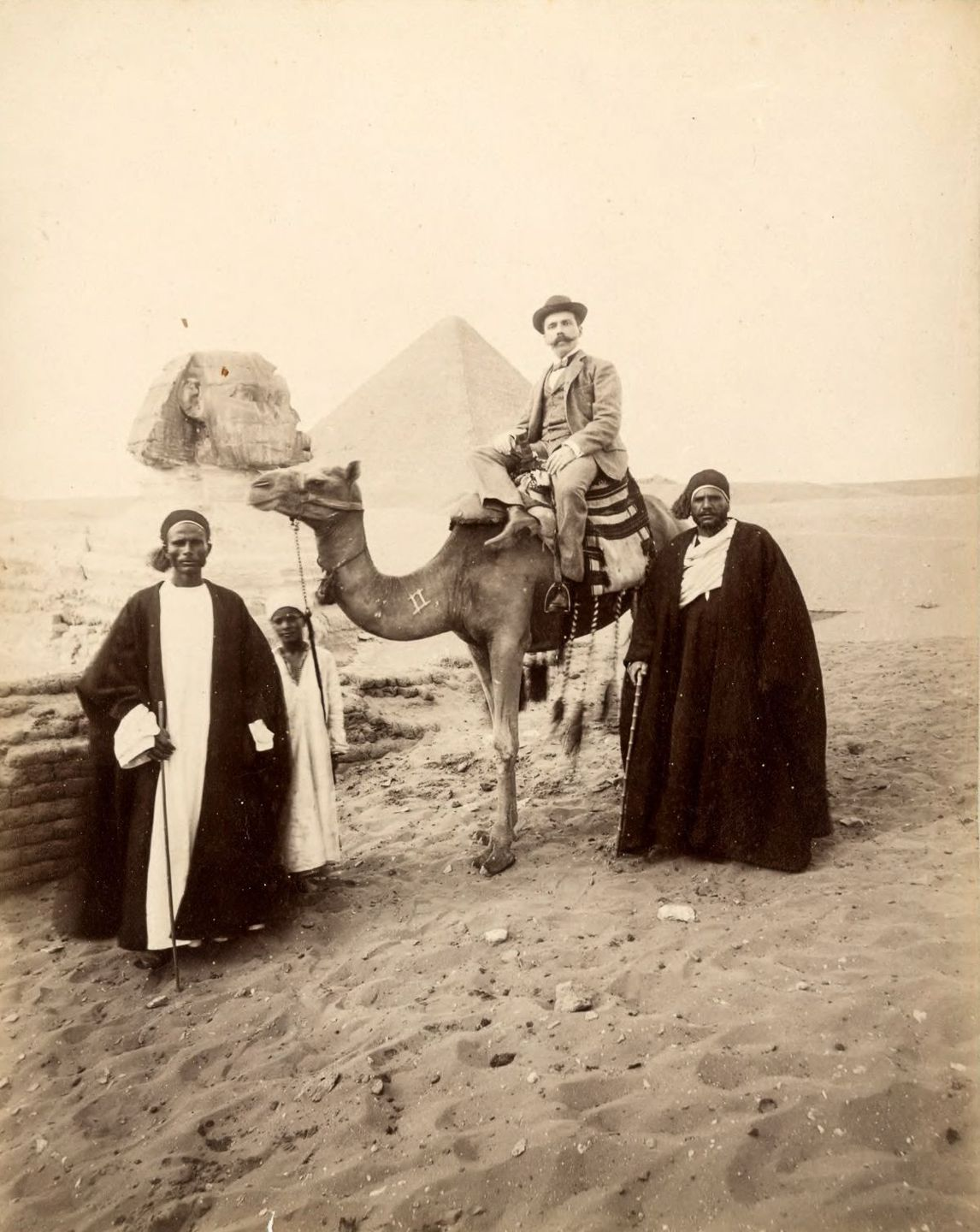 Tourist and guides with camel.