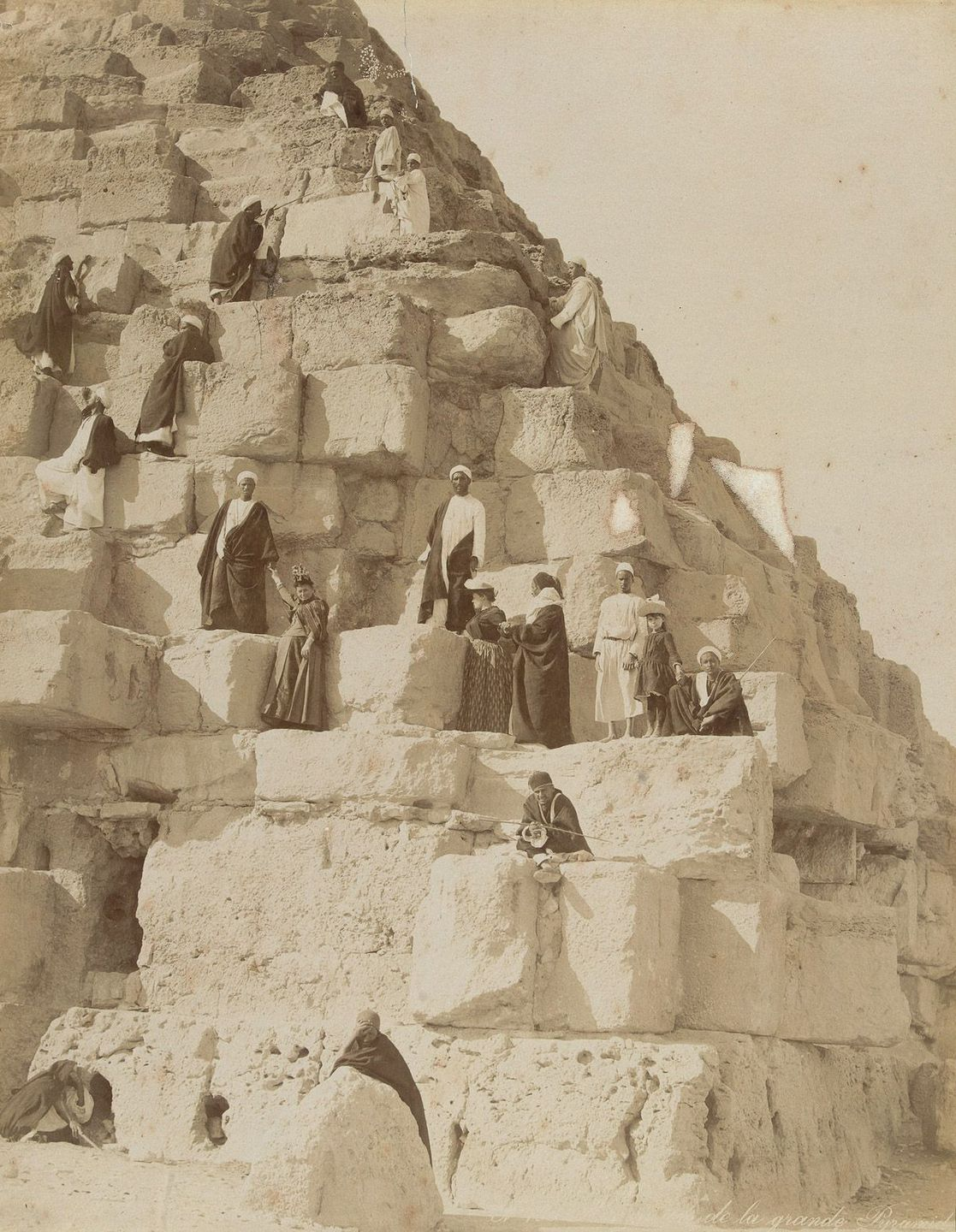 European tourists and local guides climb one of the pyramids at Giza.
