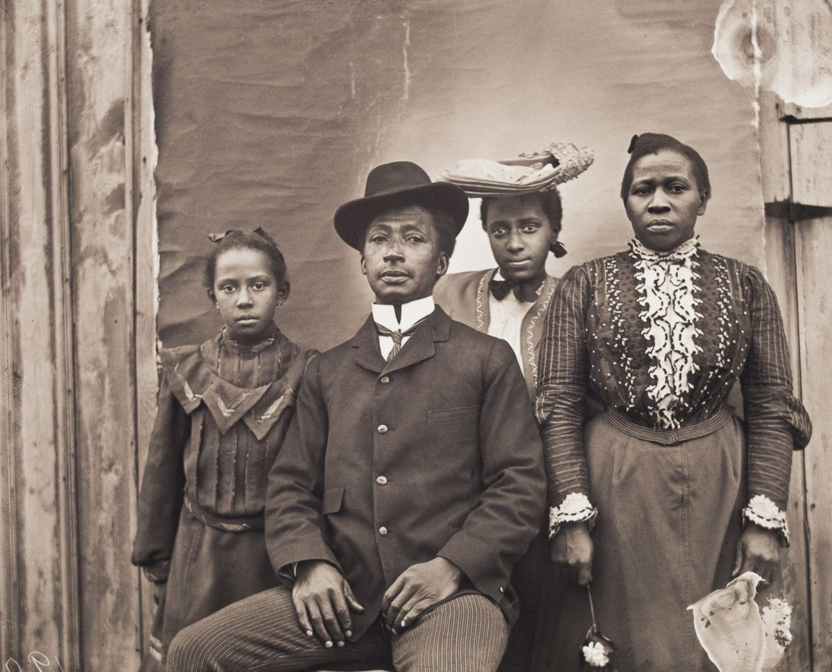 1900 Portrait of James J. and Jennie Bradley Johnson Family. James J. Johnson, of Nipmuc, Narragansett, and African American descent, and Jennie Bradley Johnson, a migrant from Charleston, South Carolina, pose with their daughters Jennie and May. James worked as a coachman and belonged to the King David Masonic Lodge. He died soon after this portrait was taken. Jennie later worked as a laundress.