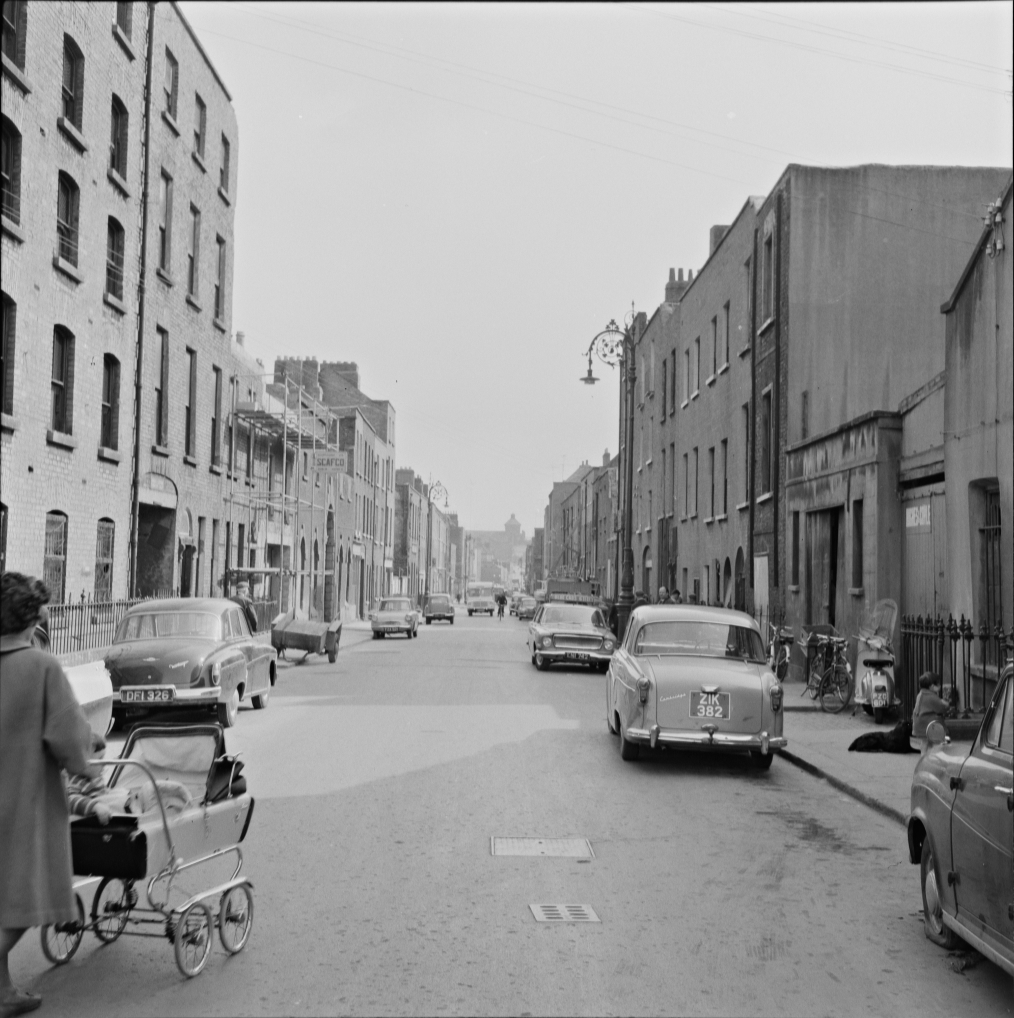"Ireland 1960s, Queen Street, Dublin City, Co. Dublin As I was uploading this I had a strange sense that I was seeing a case of ""deja vu"" all over again. Queen Street, in the ancient heart of Dublin's north side, as it was in 1964. It is one of many streets that have changed utterly in the meantime. Apart from corroberating how this part of Dublin has changed in recent decades, there was an interesting discussion today on the cars in this photo. Specifically, there seem to be several models which might've been more common in East Berlin than in North Dublin. Including Wartburg and DKW examples. There's an intruiging suggestion that the cars may have been used during filming of 'The Spy Who Came in from the Cold' (1965) in which Smithfield doubled for Cold War Berlin. However the dates may not fully add-up. A nice thought though..... Photographer: James P. O'Dea Collection:James P. O'Dea Date: 16 May 1964"