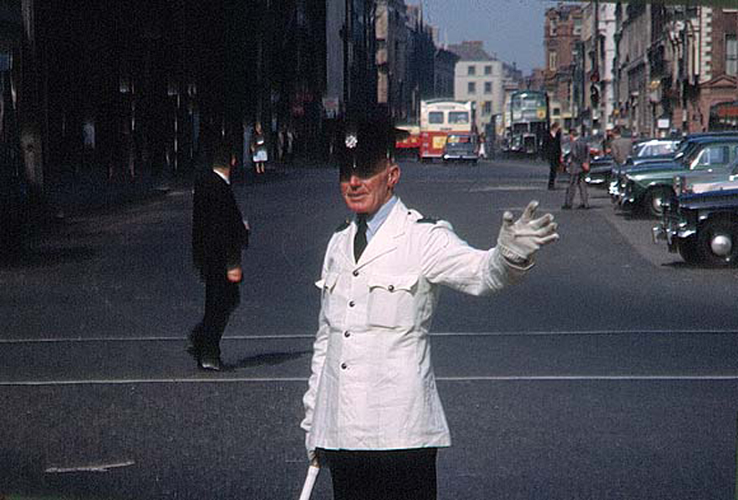 "Ireland 1960s, A Garda directing traffic on Dame Street in Dublin. This just in from freethedub who says: ""Looks like my grandfather who was stationed in Pearse Street Station, Garda Patrick Chambers until his retirement in 1969."" Date: June 1963"
