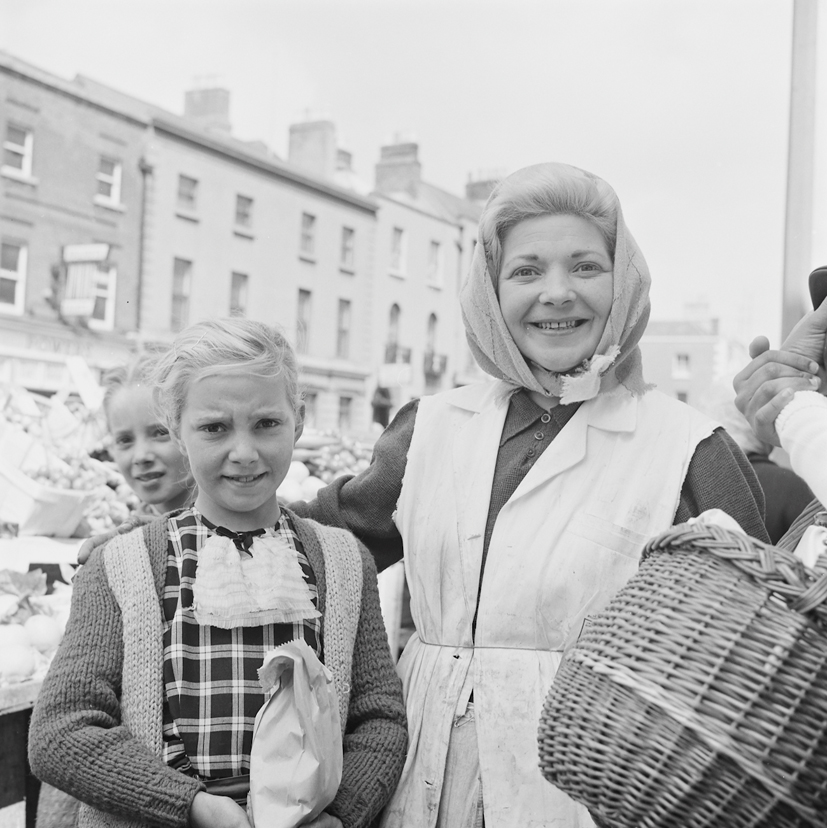 Ireland 1960s, This woman is one of the most vibrant portraits in our collections. The girl with her in the check dress appears in another Wiltshire shot, taken in Moore Street, Dublin on the same day. The basket holder to the right is held by the woman in that photo. Looks to me as if the smiling woman is a stall holder. Would love to identify either of both of these Mystery Shoppers... Photographer: Elinor Wiltshire Date: 1964