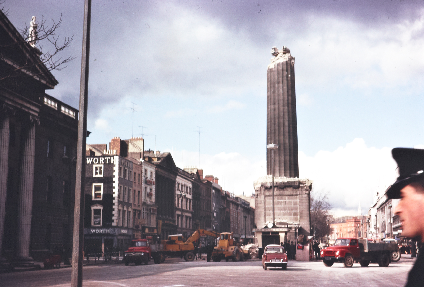 "Ireland 1960s, A half-demolished Nelson's Pillar on O'Connell Street, Dublin. From the front page of the Irish Times on Tuesday, 8 March 1966: ""The top of Nelson Pillar, in O'Connell street, Dublin, was blown off by a tremendous explosion at 1.32 o'clock this morning and the Nelson statue and tons of rubble poured down into the roadway. By a miracle, nobody was injured, though there were a number of people in the area at the time."" Date: Tuesday, 8 March 1966"