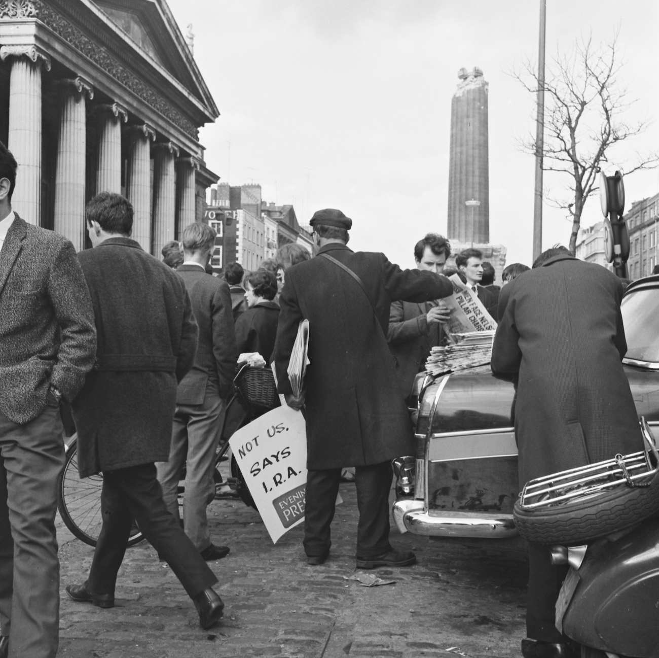 Ireland 1960s, An Evening Press newspaper seller does a brisk trade on O'Connell Street, Dublin on the day after Nelson's Pillar was blown up. Photographer: Elinor Wiltshire Date: Wednesday, 9 March 1966