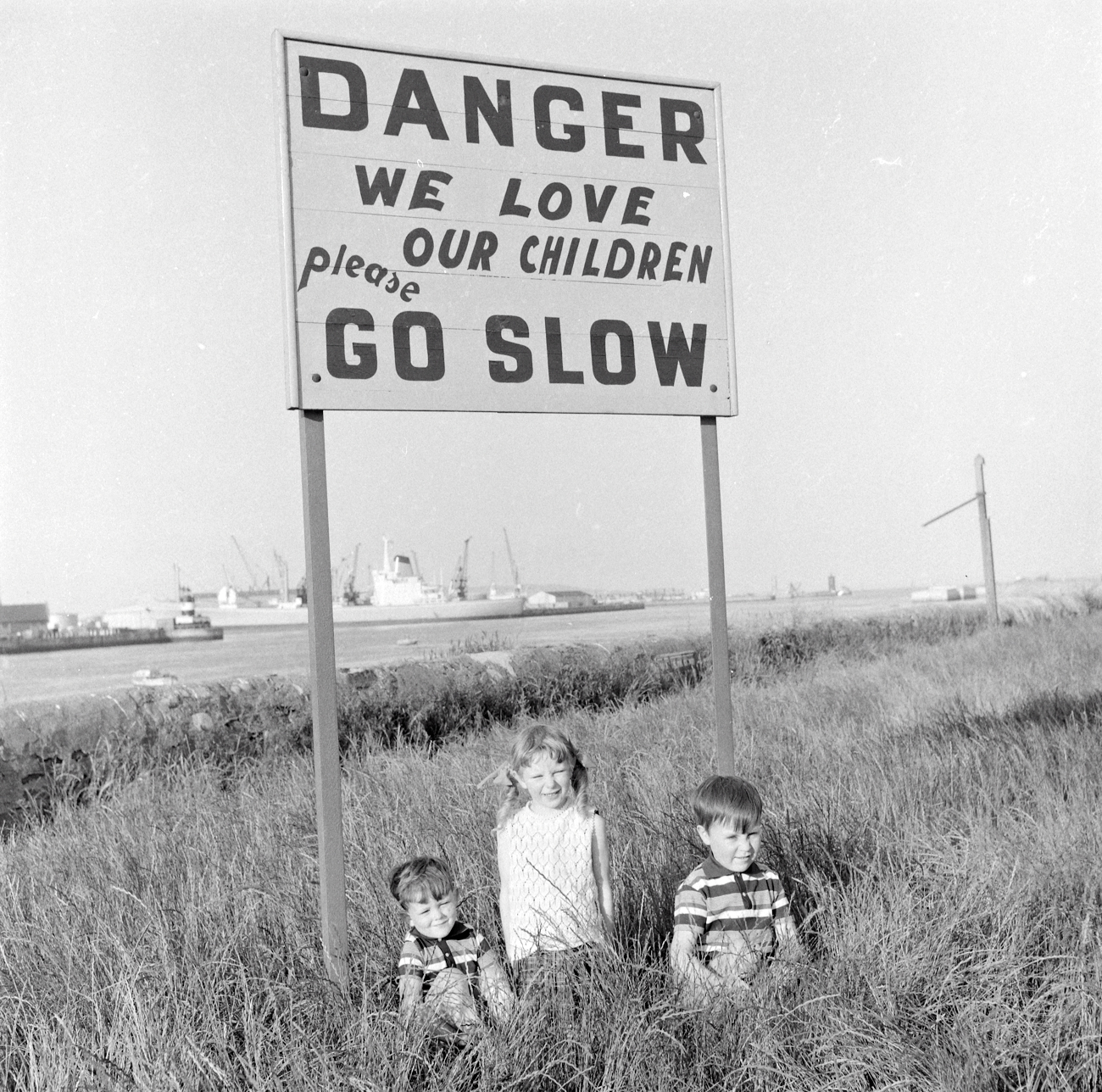 Ireland 1960s, Children under a sign designed to protect them on the Pigeon House Road, Ringsend, Dublin. Photographer: Elinor Wiltshire Date: 1969