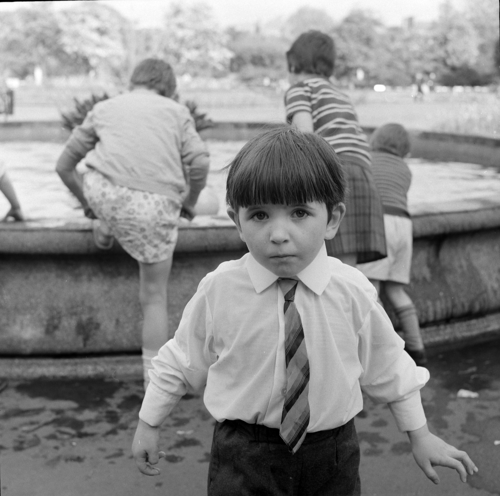 Ireland 1960s. Any of you familiar with St. Stephen's Green in Dublin will recognise the fountain behind this little chap. It's the one where the water emerges from bulrushes. Photographer: Elinor Wiltshire Date: 1964