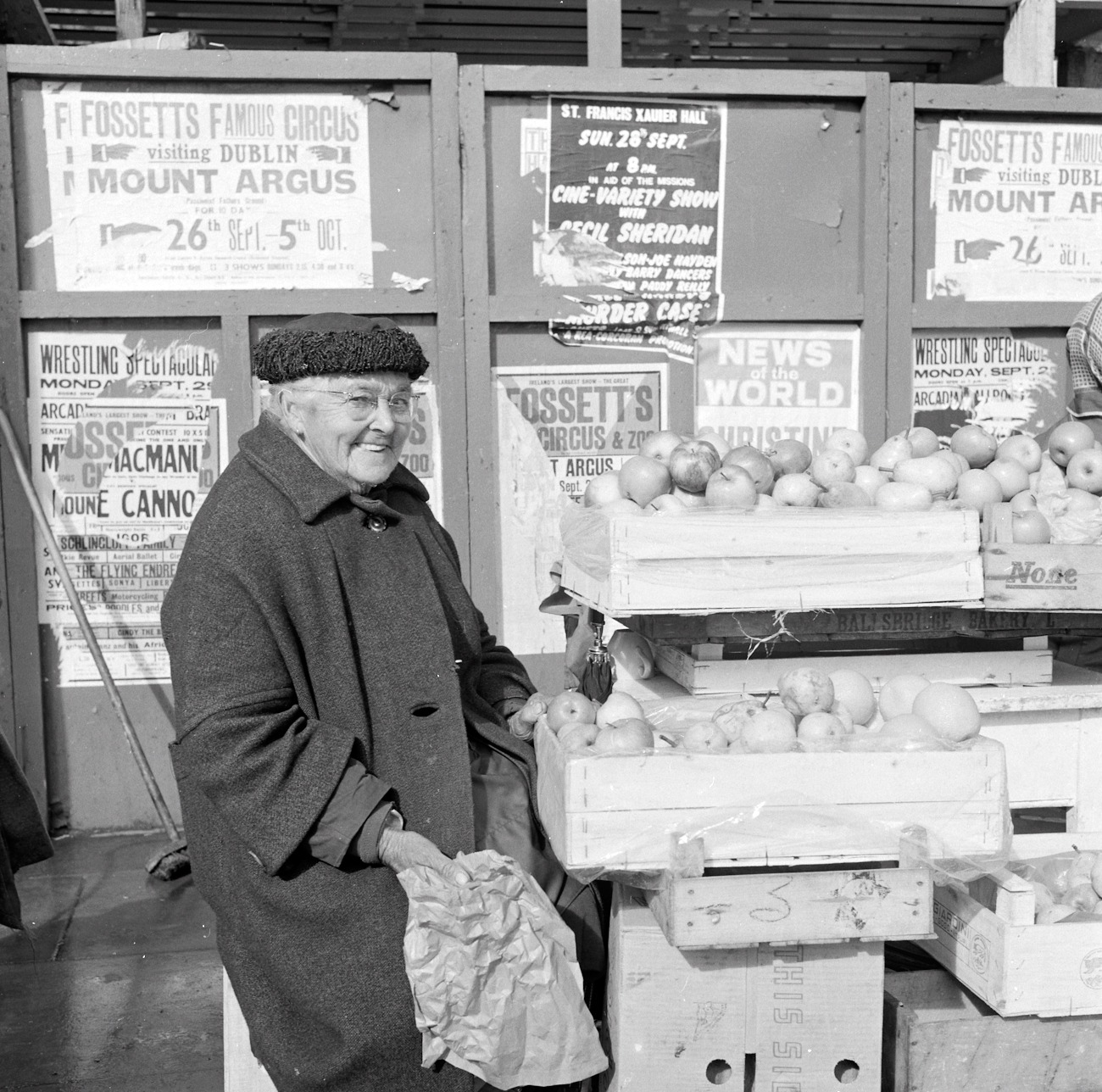 Ireland 1960s, Fruit seller with a very cheeky grin. We originally thought this photo was taken outside Heuston Station (previously Kingsbridge), Dublin, but see comments below showing it was taken alongside the hoarding around the site of the blown up Nelson's Pillar on O'Connell Street. It was definitely taken on the day of a G.A.A.match - perhaps the All-Ireland Final, given the dating evidence from the posters in the background. Anyone know this lady's name? Photographer: Elinor Wiltshire Date: September 1969