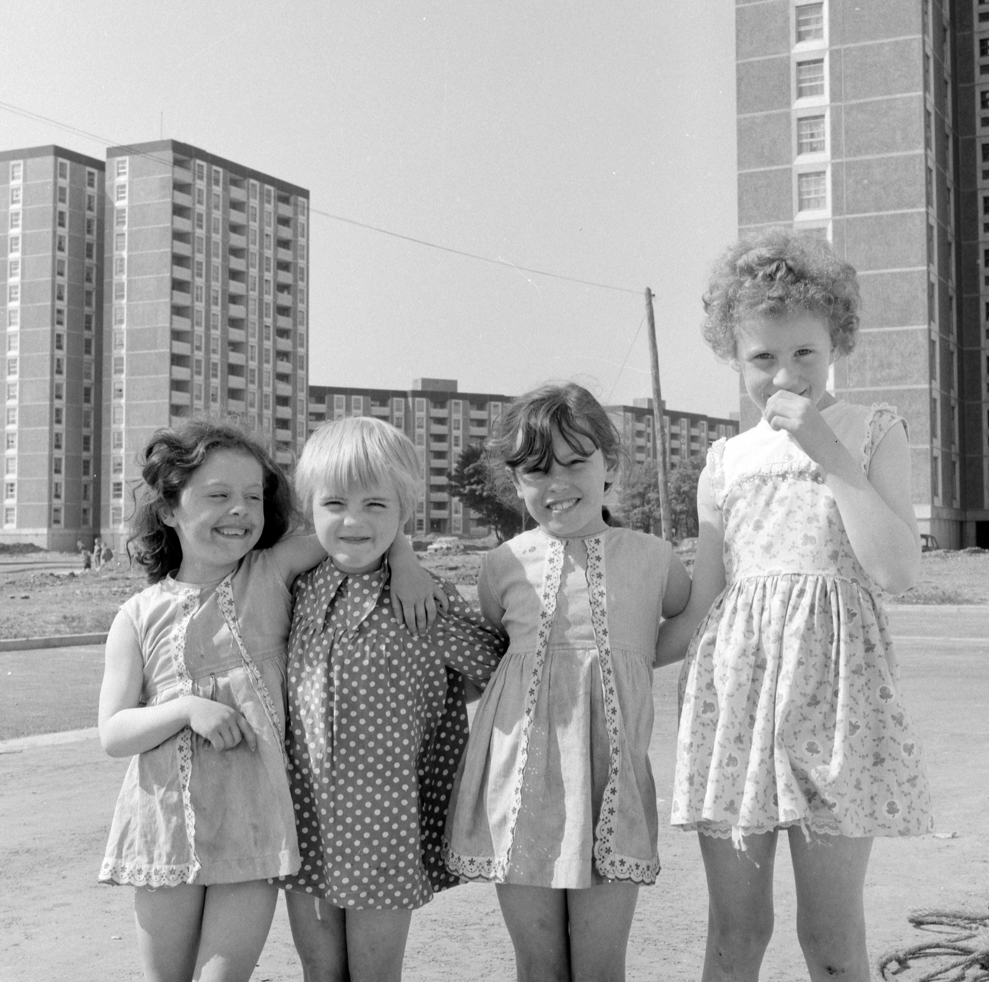 "ireland 1960s Four little girls in the shadow of the Ballymun tower blocks. This charming image of four youngsters posing for a photograph in the shadow of the Ballymun towers back in 1969 would brighten any Wednesday morning! The 'flats' had just been opened, the families had moved from the crowded and sub-standard housing of the inner city to the brave new world of the new apartments and everybody was full of hope for a bright future. This was before the blight of drugs and addiction, before the ""troubles"" and the escalation of violence that came with them and hope sprang eternal! I wonder are they still in Ballymun and has life treated them kindly? Photographer: Elinor Wiltshire Date: 1969"