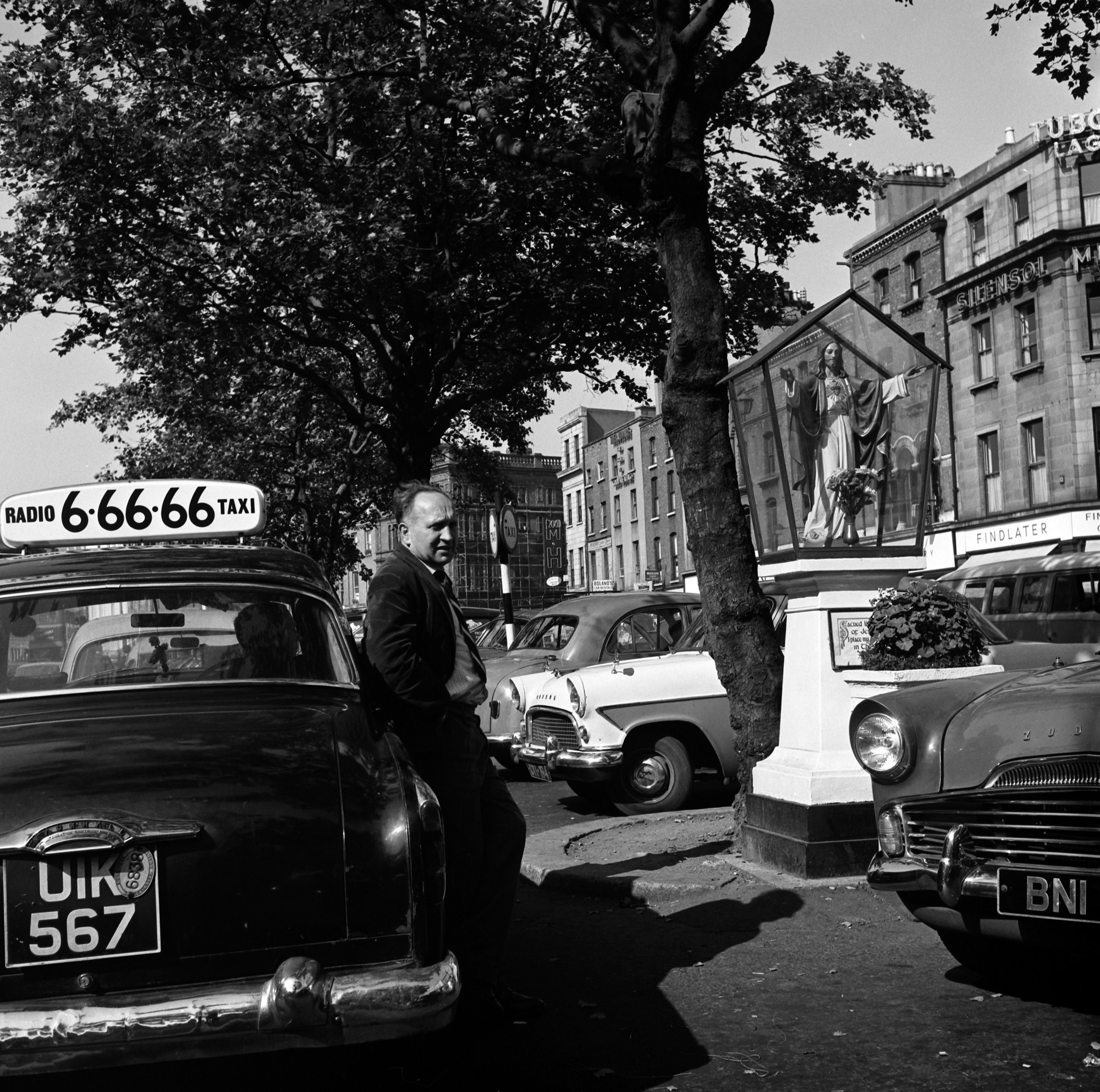 Ireland 1960s, Taxi driver waiting for a fare (and chatting to another driver leaning on his car?) at the rank in Dublin's O'Connell Street beside the Sacred Heart Shrine. Photographer: Elinor Wiltshire Date: Summer 1964