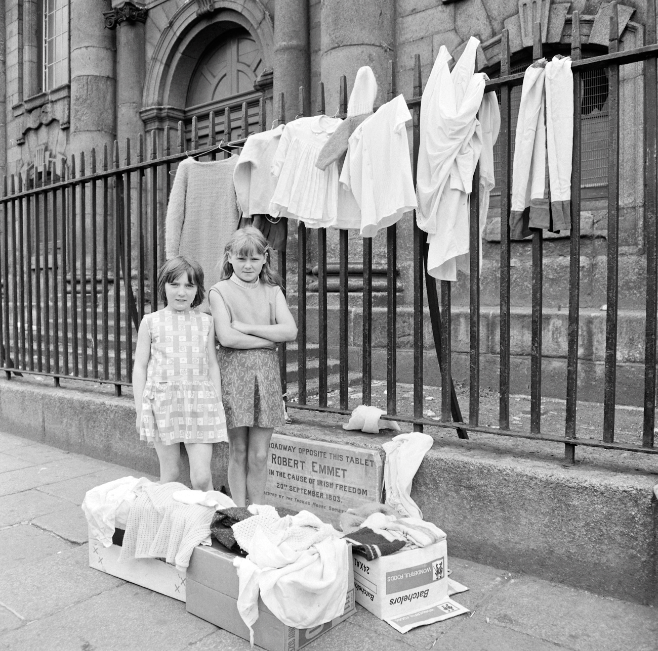 "Ireland 1960s, These two young entrepreneurs had set out their ""stall"" in front of St. Catherine's Church on Thomas Street in Dublin. Said this morning that it would make an old library very happy if these girls could be identified, and we've done it! Thanks to the sister of one of them, we now know these are Elizabeth or Lily Collins on the left, and her friend Angela Arnold on the right... Photographer: Elinor Wiltshire Date: Summer 1969"