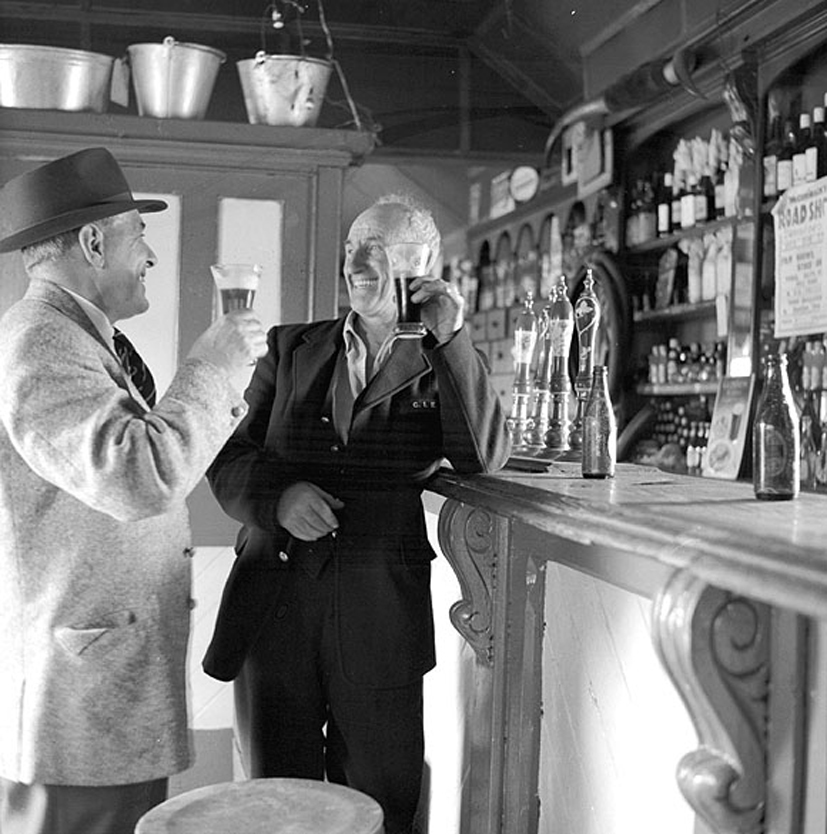 Ireland 1960s, This is James P. O'Dea (left) and Fred McDonagh raising a glass at a pub in Moyvalley, Co. Kildare. By the looks of the CIÉ logo on Fred's jacket, he was one of the many railway workers all over Ireland, who would have known James very well. Originally, we just knew the railwayman as Fred, but his grandson Traingraham identified him as Fred McDonagh, who lived in the station in Moyvalley till he died on 7 July 1977. A couple of commenters have suggested that this was Furey's Pub in Moyvalley. James O'Dea was the photographer responsible for many of the train and railway photos you'll see here on our photostream. He was a founding member of the Irish Railway Records Society in 1946. James was also nephew of the famous Dublin comedian and entertainer, Jimmy O'Dea. Date: Wednesday, 23 August 1961