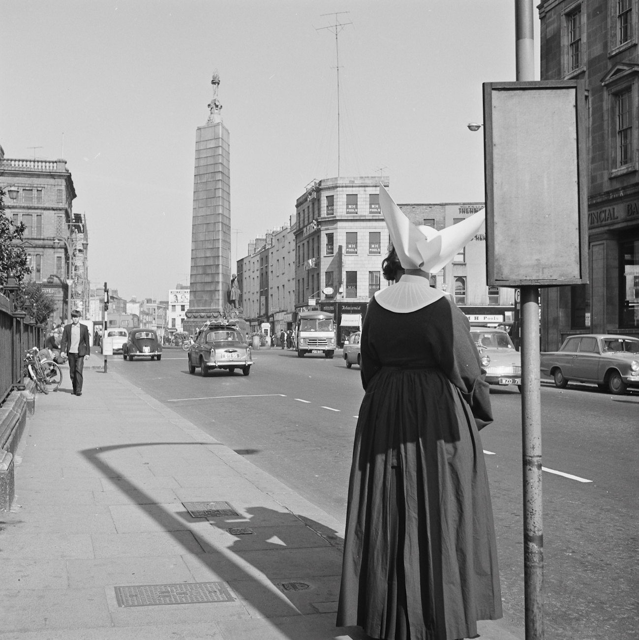 Ireland 1960s, A nun with a most remarkable (and slightly dangerous-looking) veil/head dress waiting for a bus outside the Rotunda Hospital on Parnell Street, Dublin. Cannot work out whether a clump of her own hair (unlikely) has come loose, or whether she is masking a person in front of her... With help from people over on our NLI Facebook page, it turns out this nun was a member of the Daughters of Charity (of St. Vincent de Paul). The distinctive head dress is called a cornette, and led to this order being known as the Butterfly Nuns. The Daughters of Charity abandoned the cornette on 20 September 1964, so unless this nun was ultra-traditional and carried on wearing it regardless, then this photo must have been taken before 20 September. This shot also allows us to view the Parnell Monument at the end of O'Connell Street from yet another angle. Photographer: Elinor Wiltshire Date: 1964