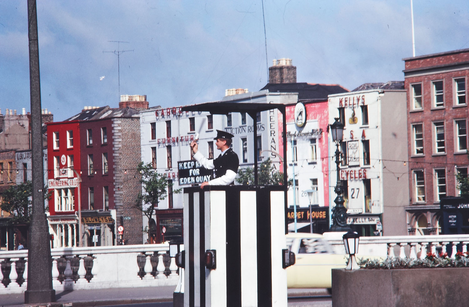 Ireland 1960s, Garda directing traffic, O'Connell Bridge, Dublin This shot gives a good view of the varied businesses on Bachelor's Walk in early 1960s Dublin. Date: June 1963