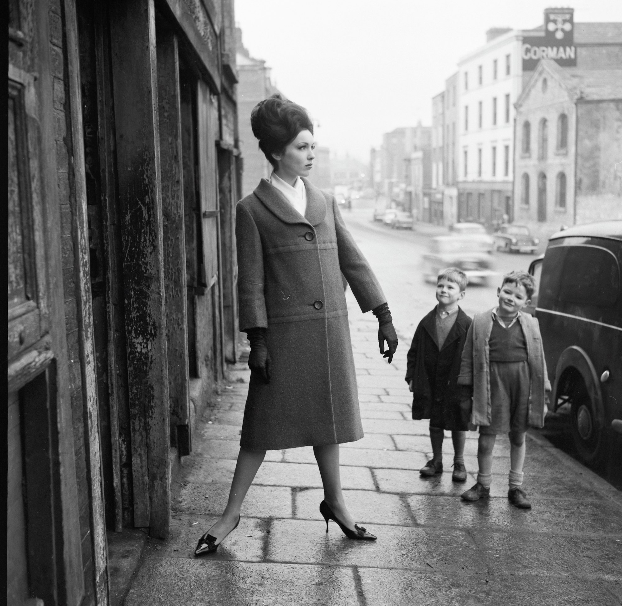 Ireland 1960s This is American model Linda Ward (later O'Reilly) posing, while two local boys give her outfit the once over… We discovered more about our elegant American model, Linda Ward, who married Brendan O'Reilly, presenter of Sports Stadium on RTÉ Television, and swapped New York for Dublin's modelling scene. Fantastically well done to derangedlemur for locating this photo at Winetavern Street, Dublin, given that the whole right hand streetscape is completely different today! Photographer: Colman Doyle Date: Between January 1960 and 1966