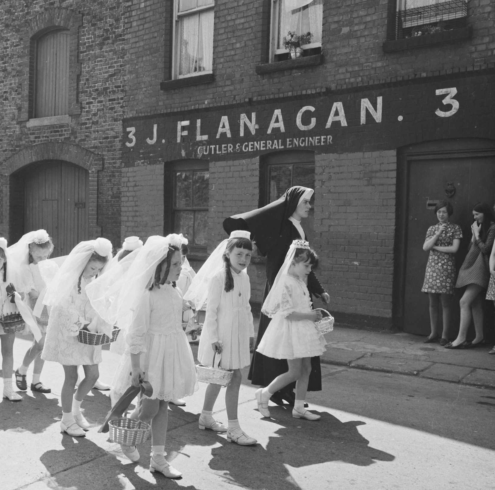 "Ireland 1960s, A young nun walking Holy Communion girls past no. 3, Halston Street, Dublin on the feast of Corpus Christi. Interesting juxtaposition with the older mini-skirted local girls. The baskets were usually filled with flower petals for the girls to scatter along the way... Thanks to Phyllis Stice over on our Facebook for allowing us to get to the exact date of 5 June 1969, from the unsatisfactory ""sometime in 1969""! Photographer: Elinor Wiltshire Date: 5 June 1969"