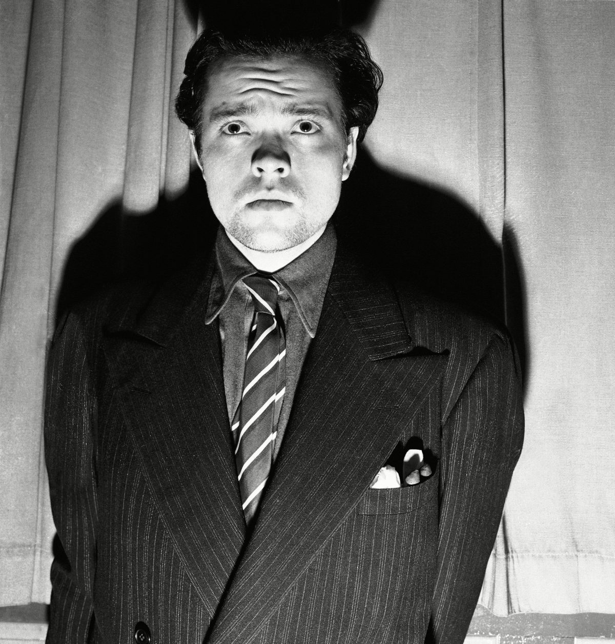 "Orson Welles, radio and stage actor, whose dramatization, of an H. G. Wells novel titled ""War of the Worlds"" which related the ""invasion"" of New Jersey by a horde of men from mars was interpreted by listeners as an actual news broadcast of the events supposed to presume the end of the world. Panicked listeners fled into streets to get away from the invaders: radio and police stations were swamped with calls all over the country - the broadcast was nation - wide (CBS) - and in Newark 15 persons were treated for shock after they rushed out of their homes to escape what appeared to be certain doom. Welles is after the broadcast Orson Welles"