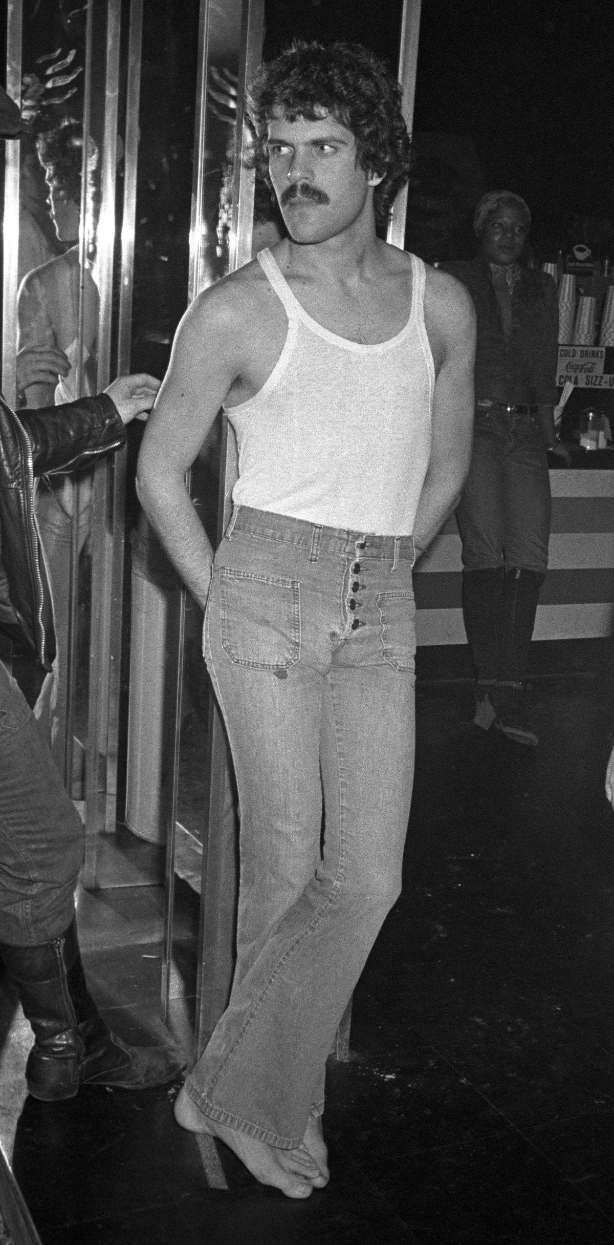 A man with a moustache wearing jeans and a tank top at the Continental Club bath house in New York - Feb 4 1972