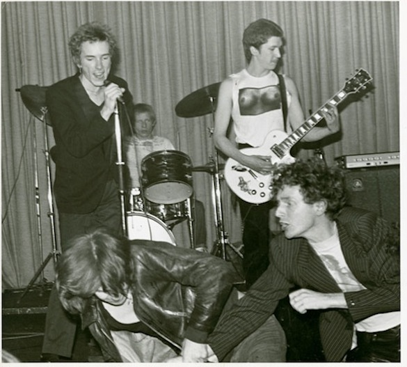sex pistols Johnny Rotten, Paul Cook and Steve Jones play on as their manager Malcolm McLaren fights with an audience member, April 23, 1976. Photo: Kate Simon