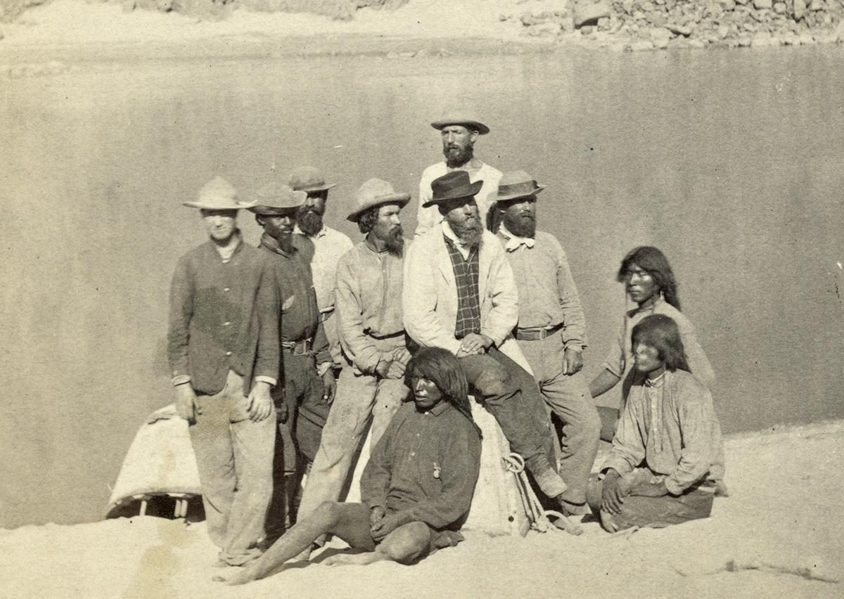 "Boat crew of the ""Picture"" at Diamond Creek. Photo shows photographer Timothy O'Sullivan, fourth from left, with fellow members of the Wheeler survey and Native Americans, following ascent of the Colorado River through the Black Canyon in 1871"