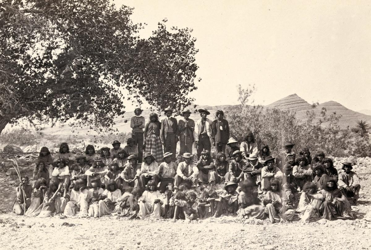 Native American (Paiute) men, women and children sit or stand and pose in rows under a tree near probably Cottonwood Springs (Washoe County), Nevada, in 1875